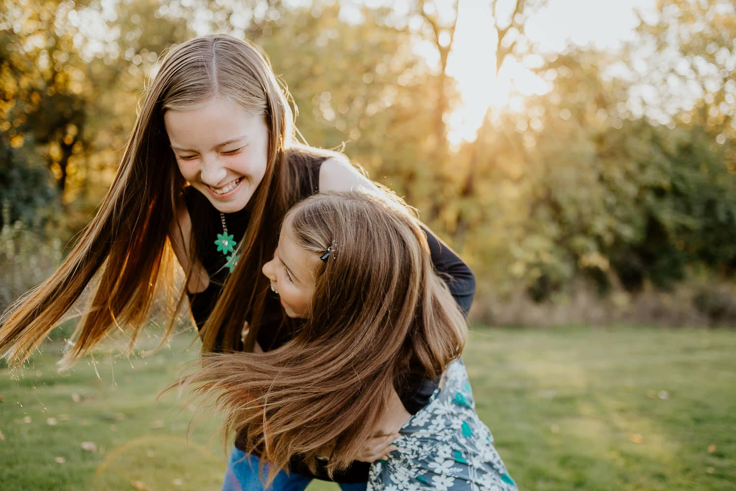 Two sisters laughing while hugging with their hair flying - Clackamas Oregon family photographer