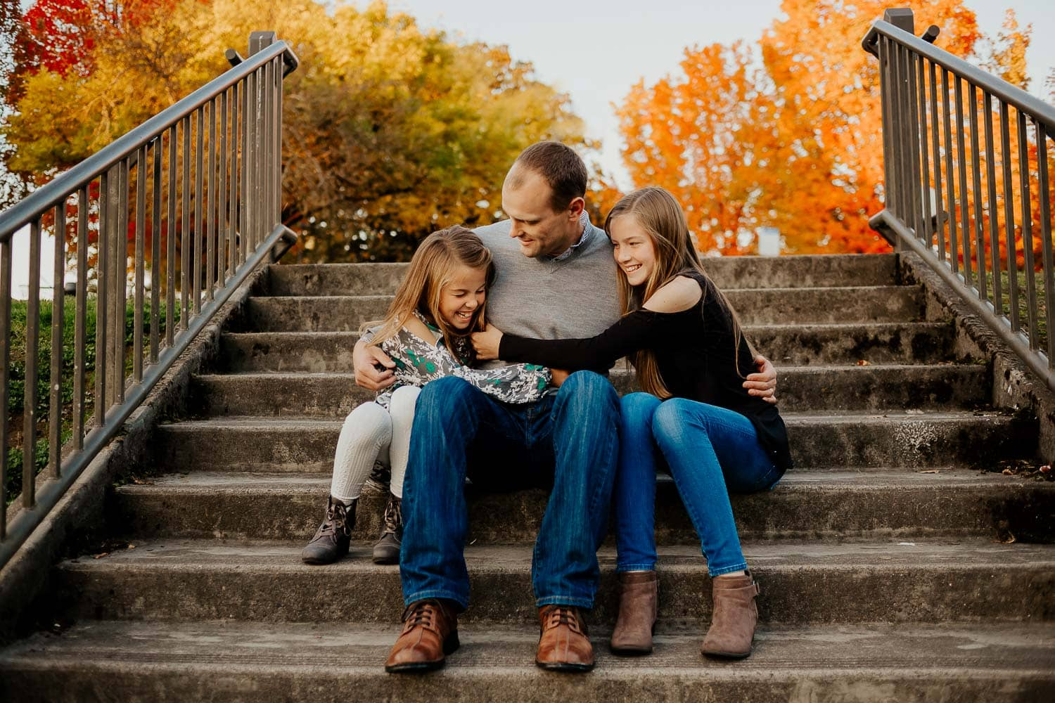 Two daughters hugging their dad while sitting on steps in clackamas oregon