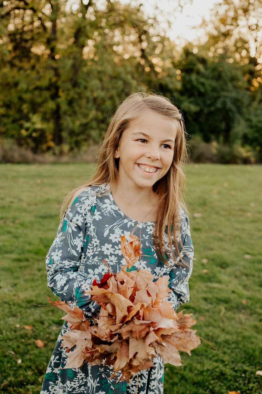 Little girl holding a pile of fall leaves - family photographer
