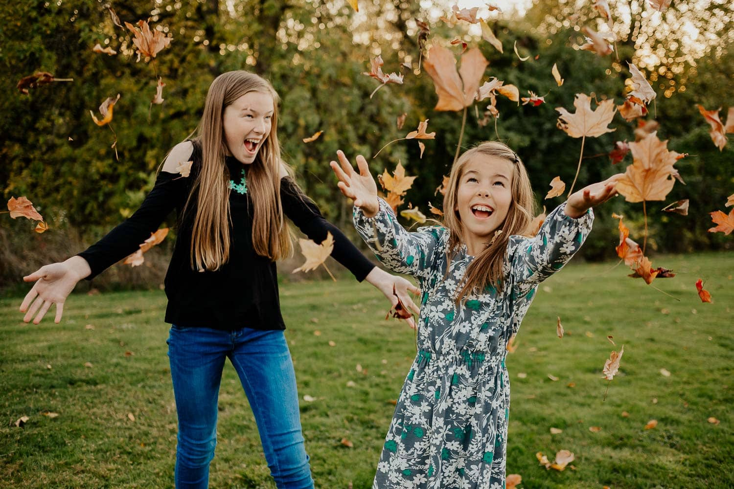 Two sisters throwing leaves and laughing in clackamas oregon