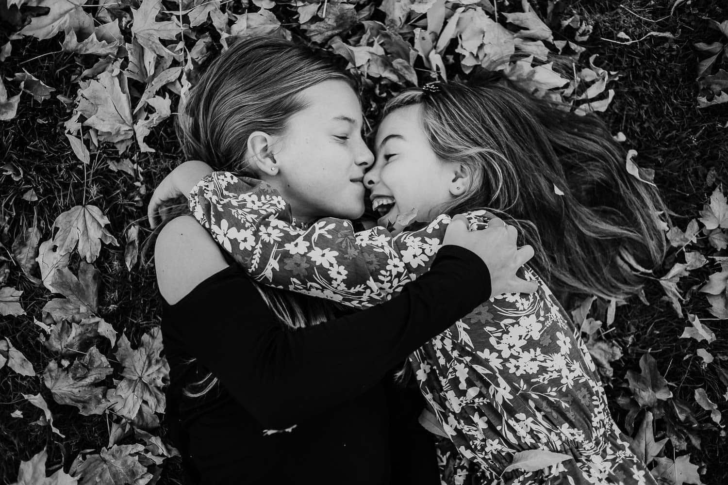 Sisters hugging in the fall leaves - clackamas family photographer