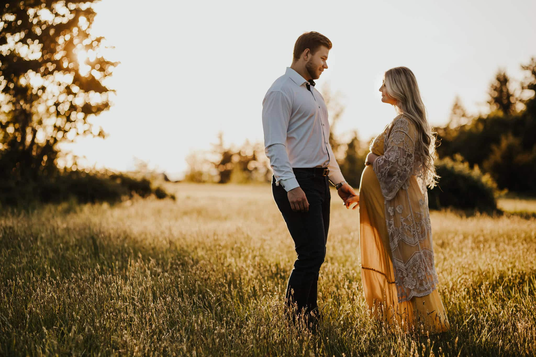 couple standing and looking at each other, holding hands - what to wear for maternity photos