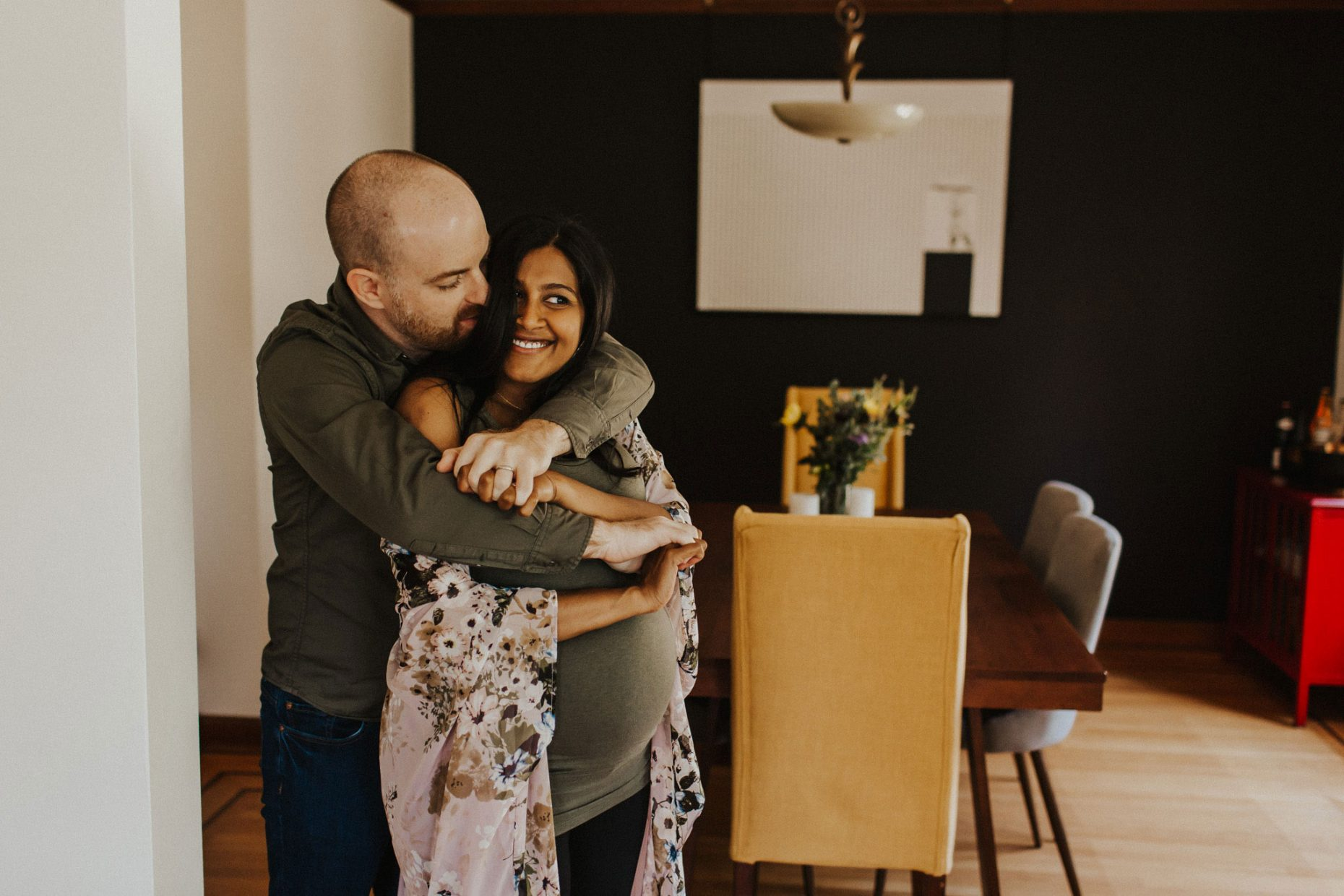 couple hugging during in-home maternity photo session