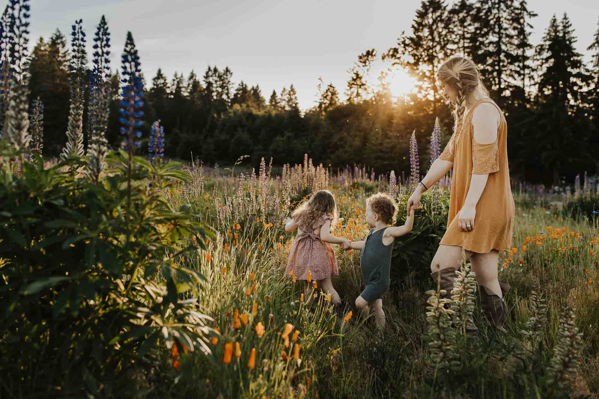 two young kids leading mom through field of flowers in the spring season - outdoor family photos in portland