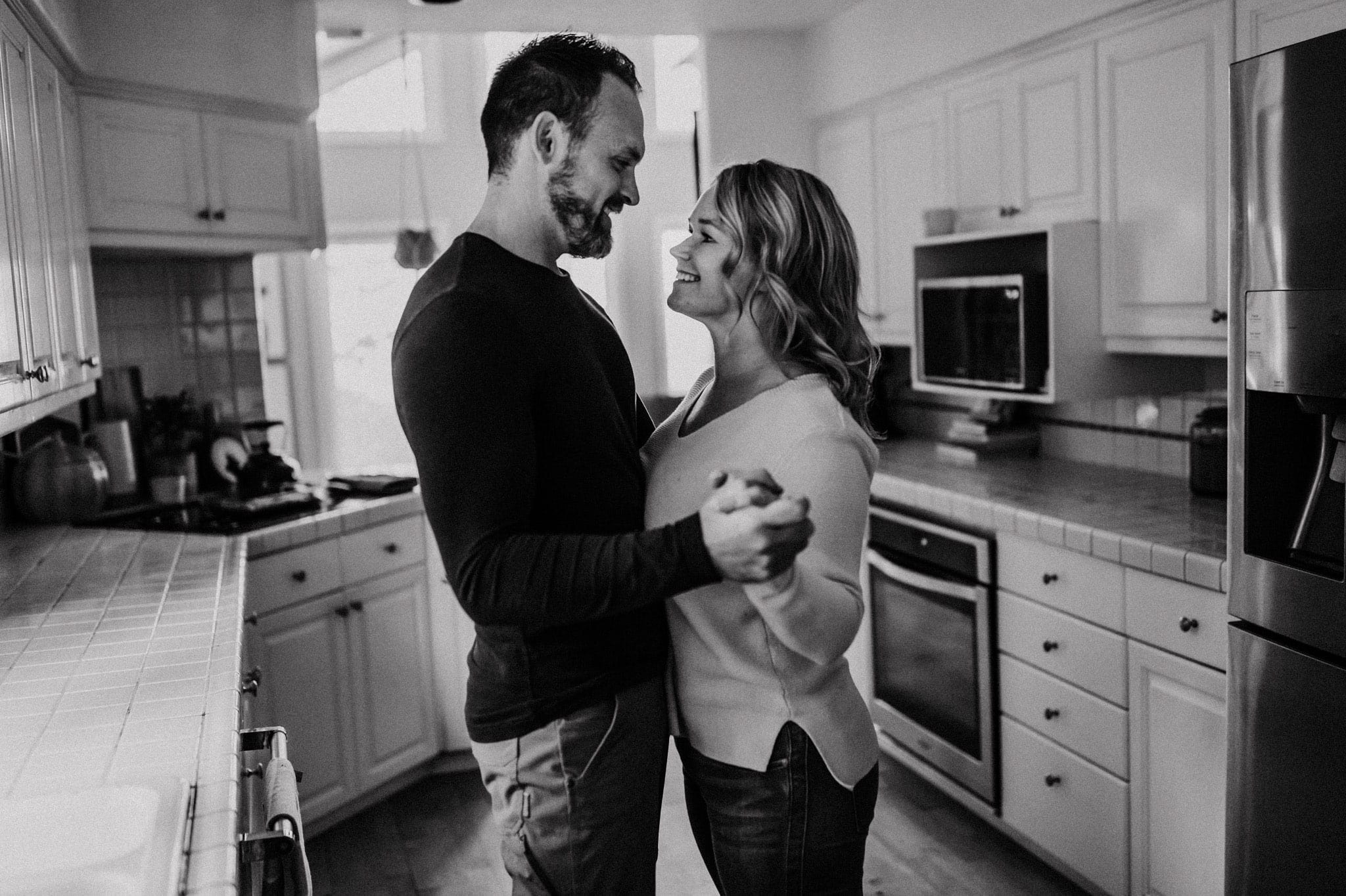 black and white photo of a couple on their anniversary dancing in the kitchen