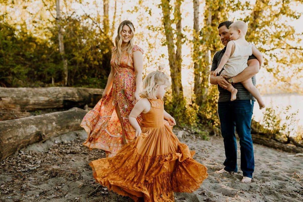 Little girl in orange Joyfolie dress twirling near a Portland river