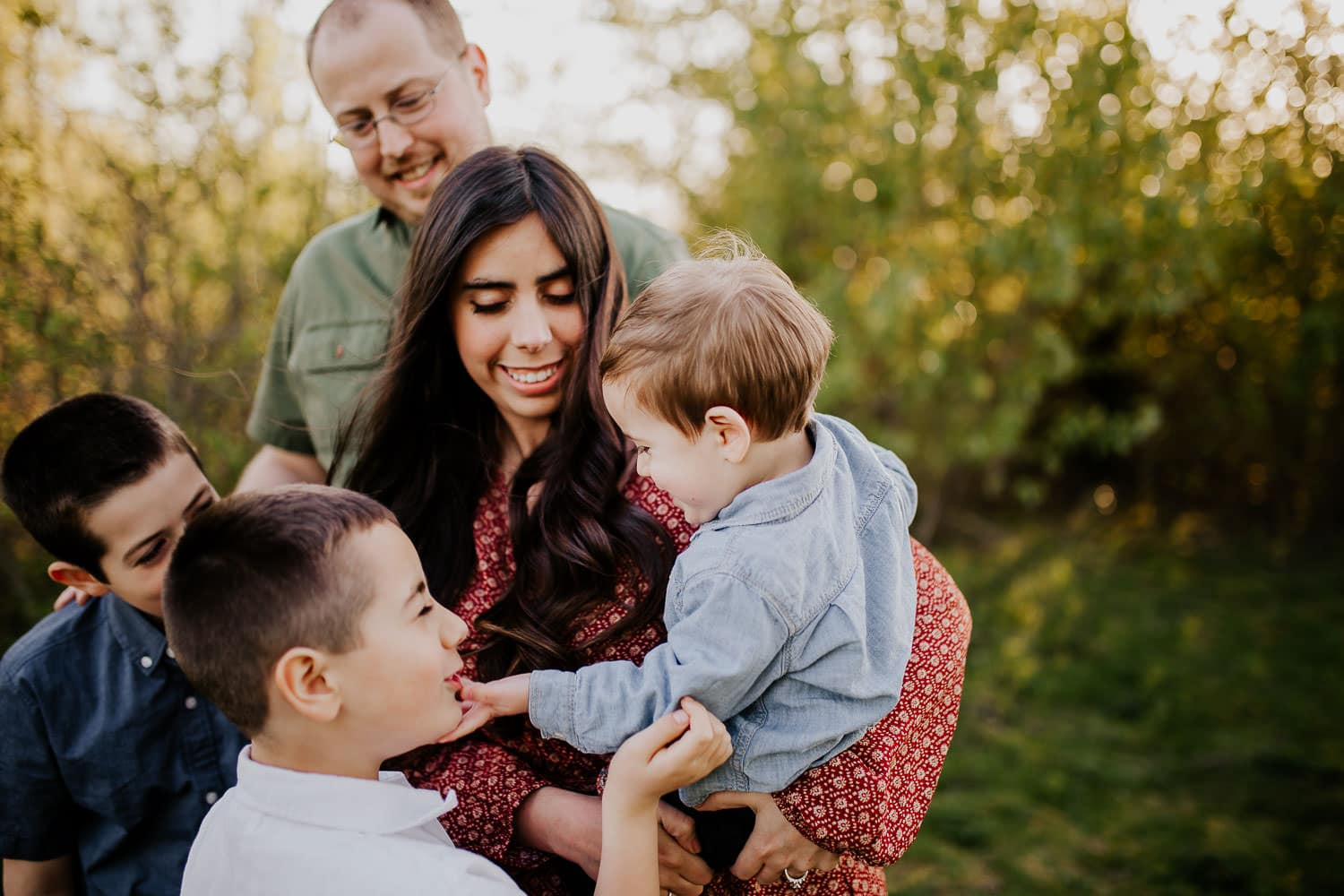 Family laughing while toddler boy grabs brothers face - Best Portland family photographers