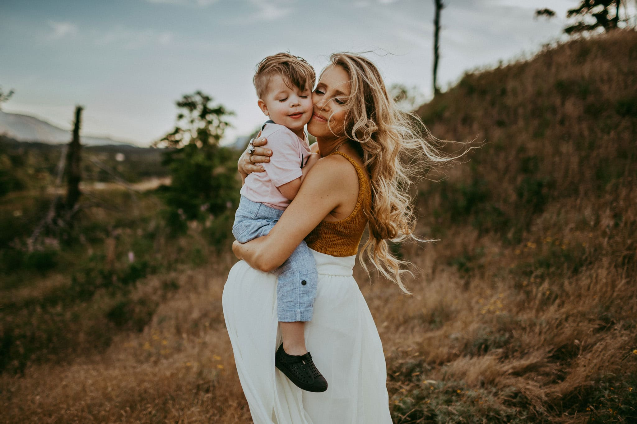 pregnant mom holding son with both eyes closed - maternity photos in portland oregon