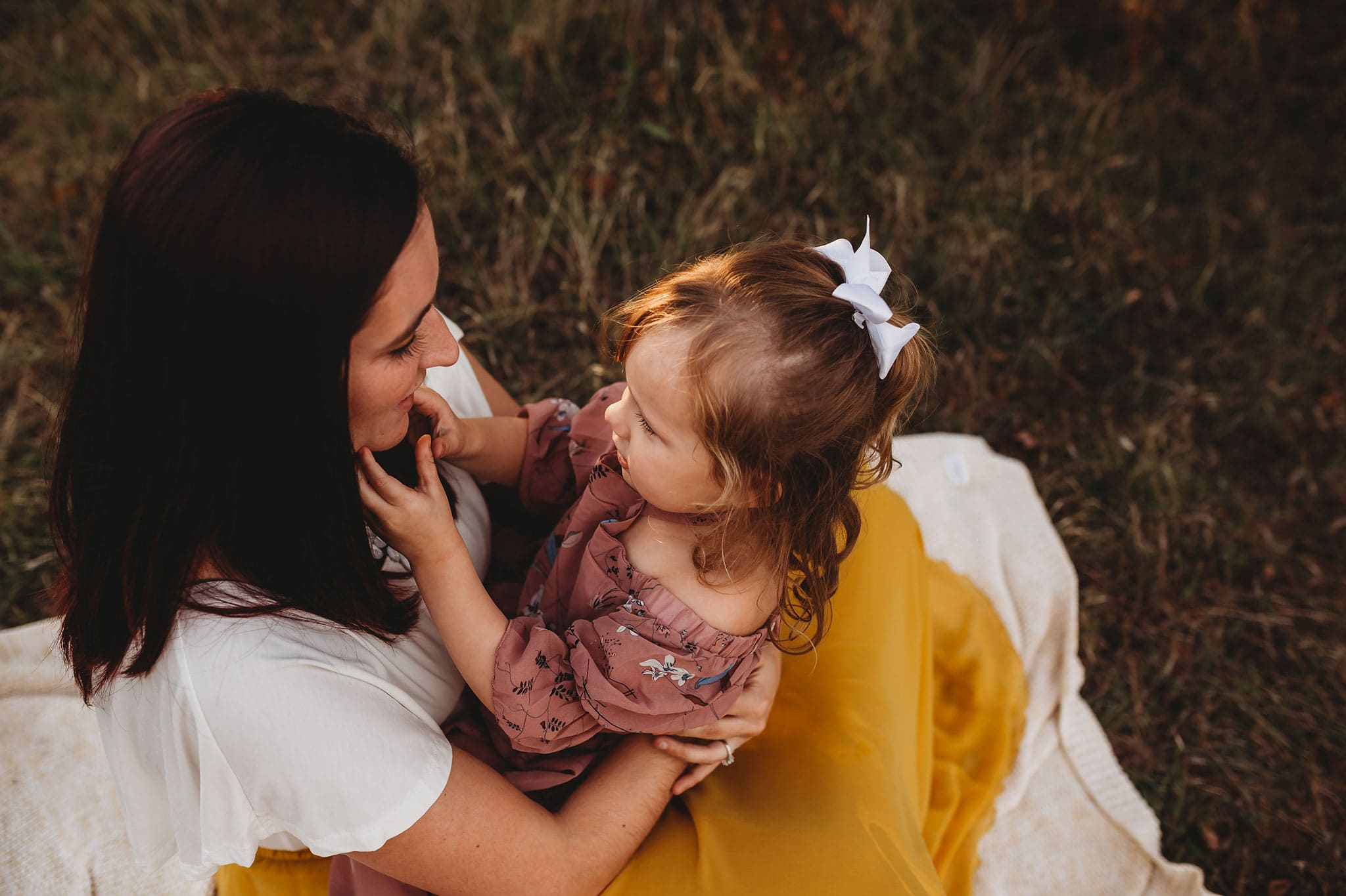 adorable little girl sitting in her mother's lap
