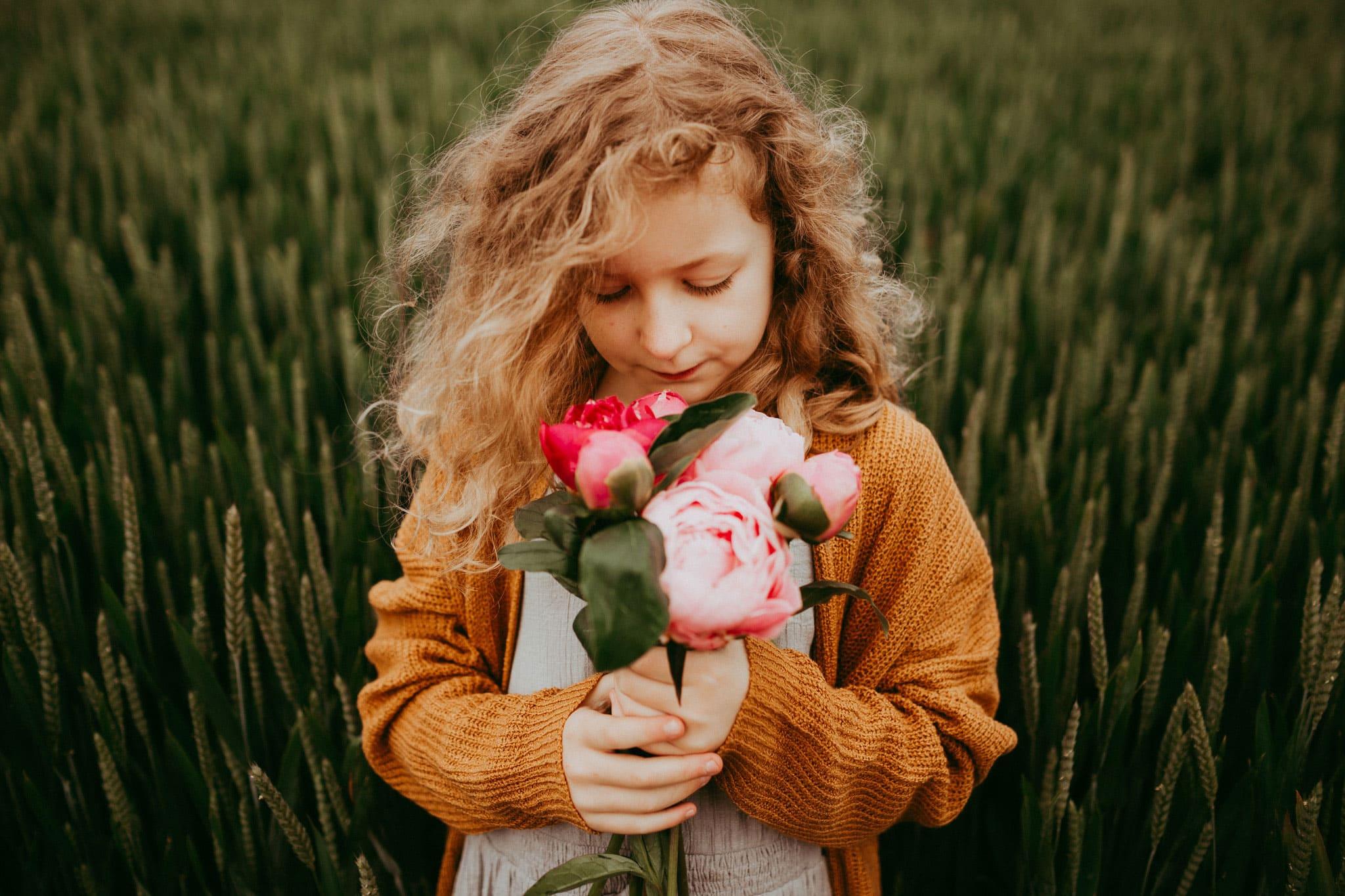 little girl holding flowers on a cloudy day