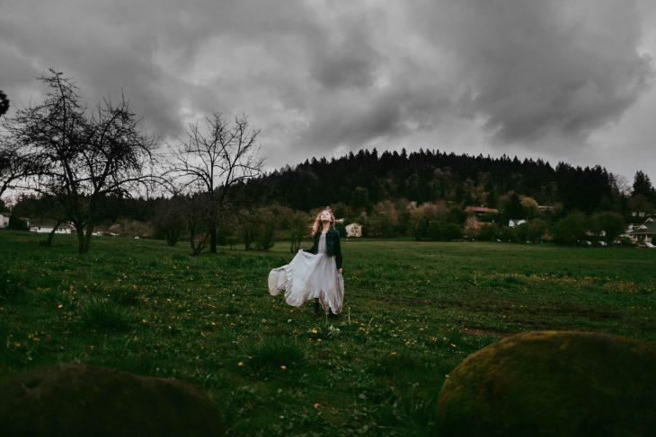 girl in joyfolie dress in field on cloudy day