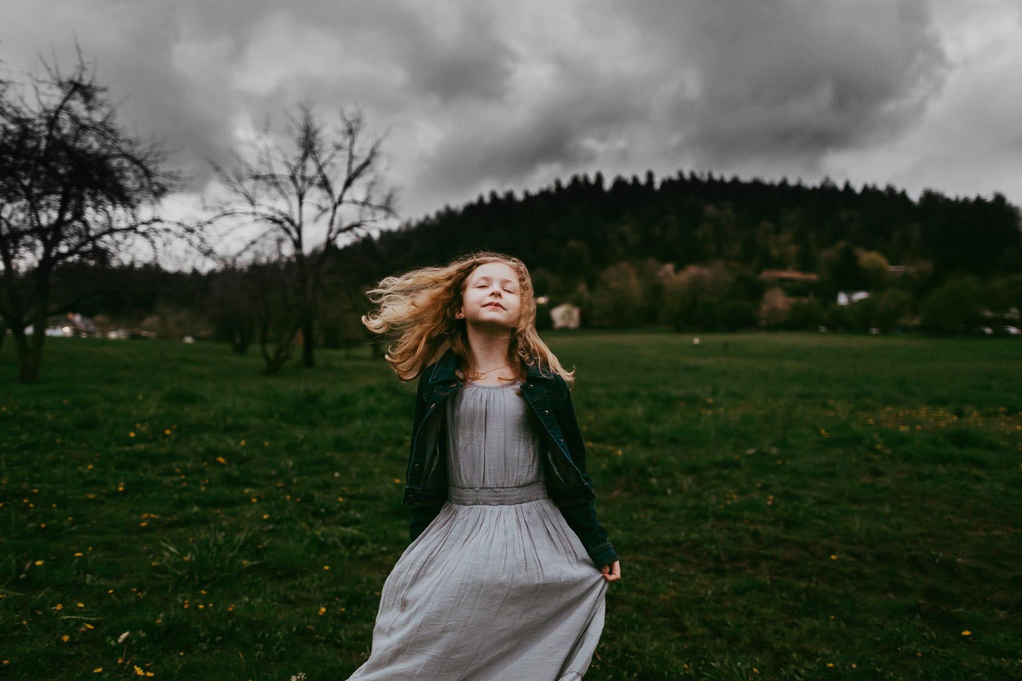 little girl in field on cloudy day in portland oregon