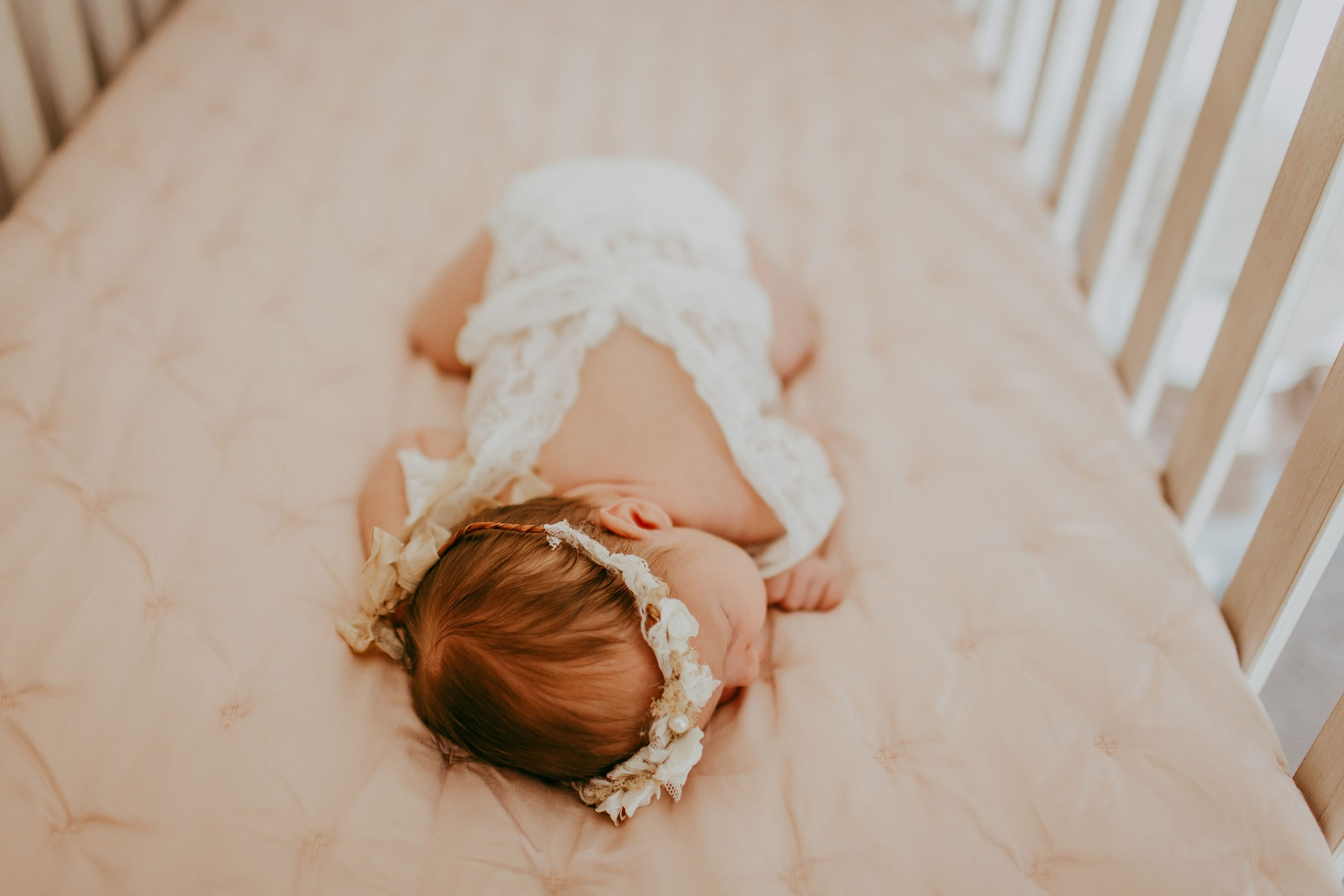 Baby in crib during lifestyle newborn photography session