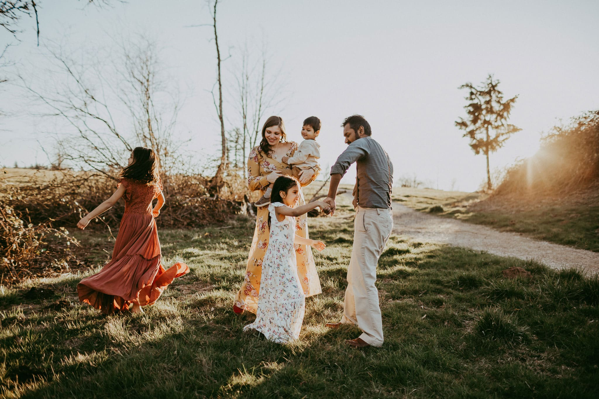 family dancing in the sun during their lifestyle maternity photography session
