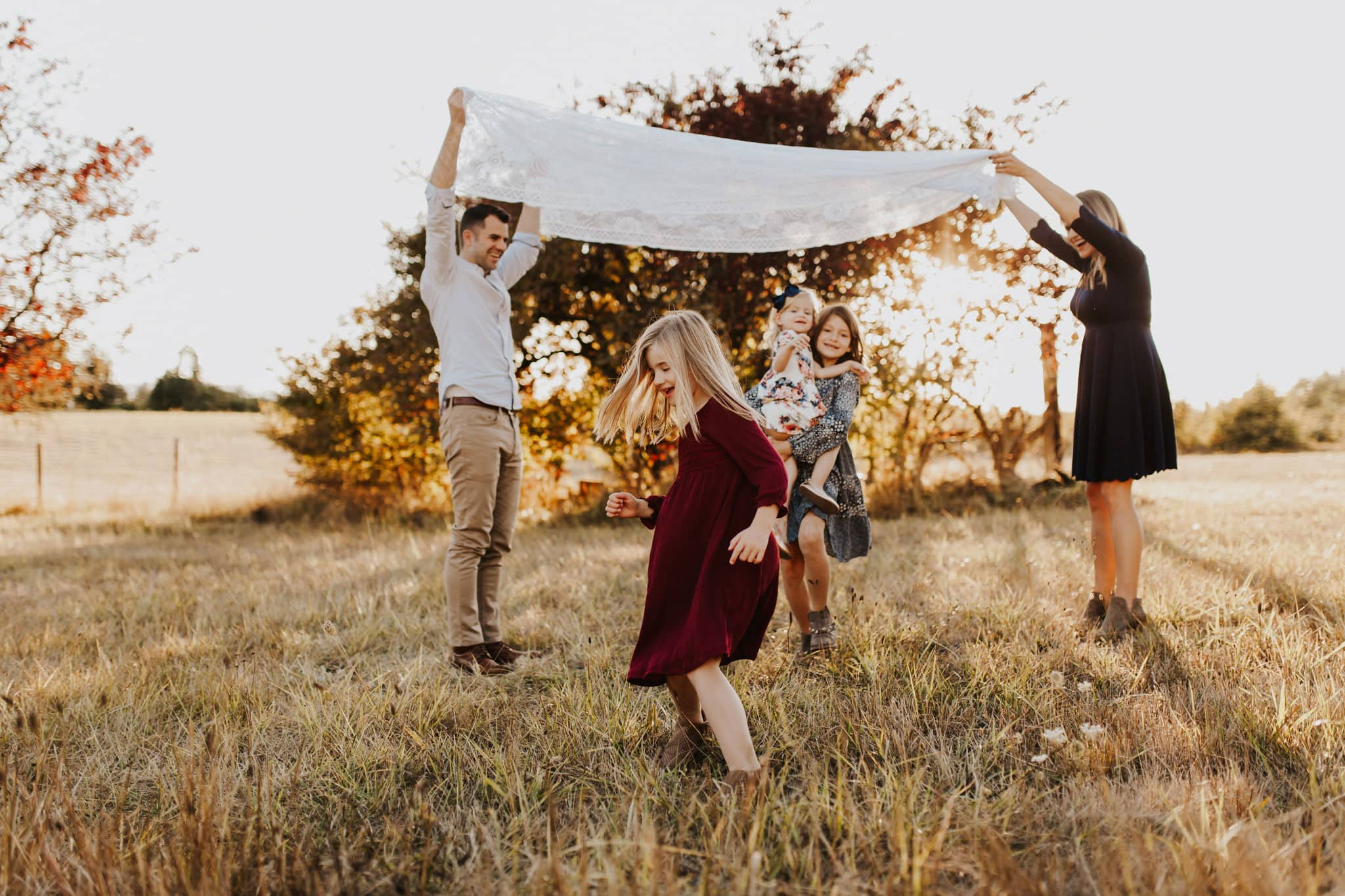 Kids running under blanket during photo session with family