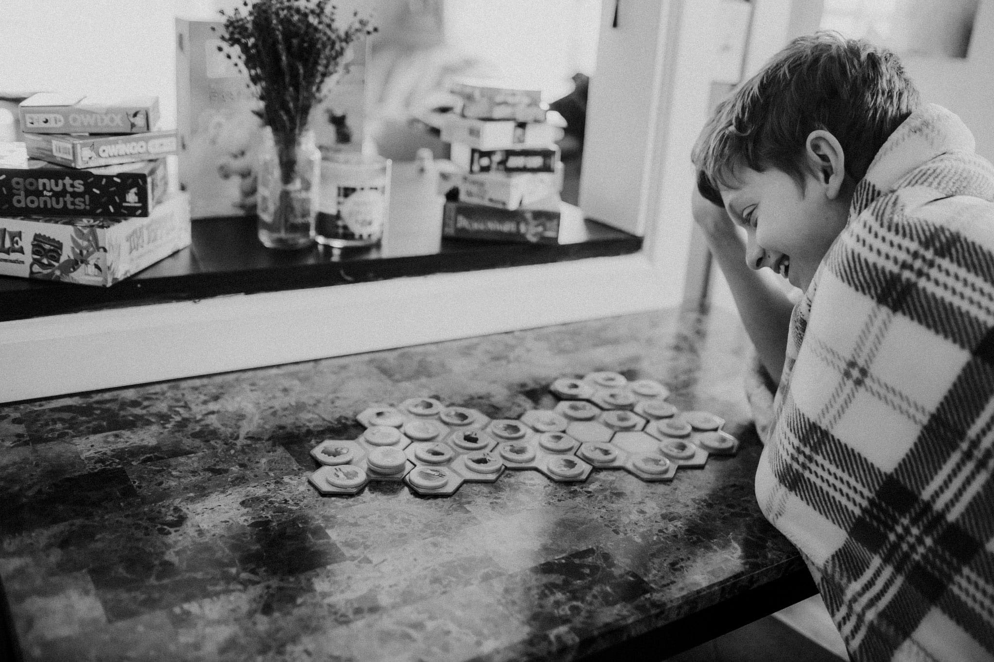 boy at table playing board games - what to do with kids when stuck at home
