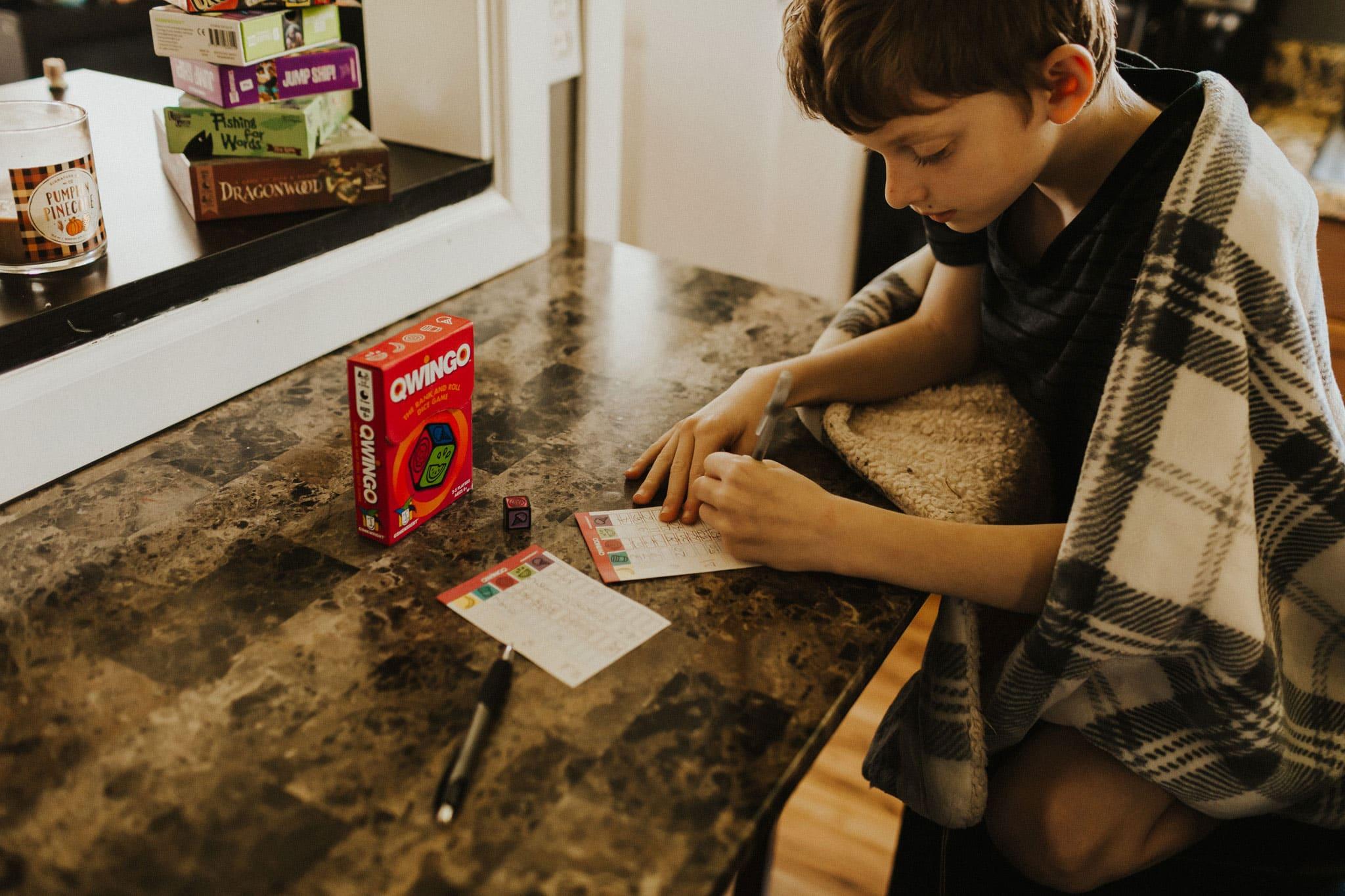 boy playing qwingo, a fun family game