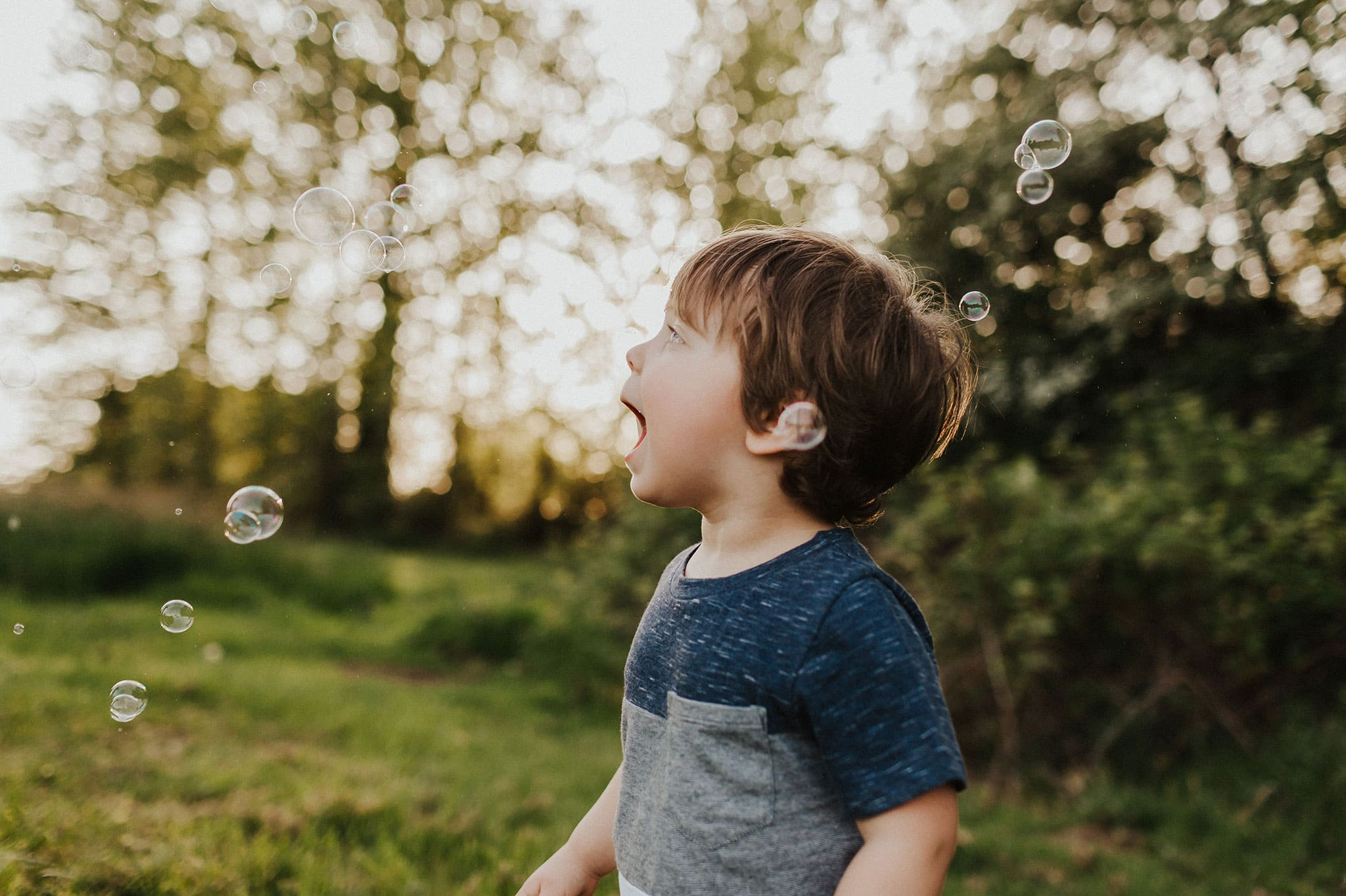 Boy trying to catch bubbles