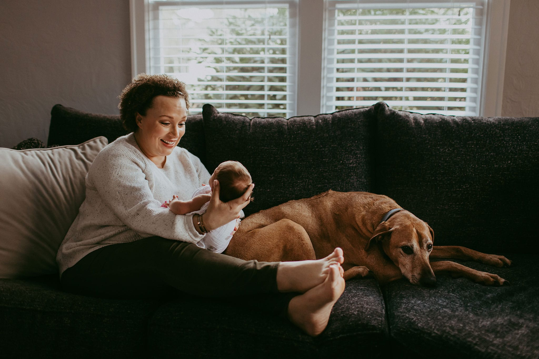 new mom, baby, and dog on couch