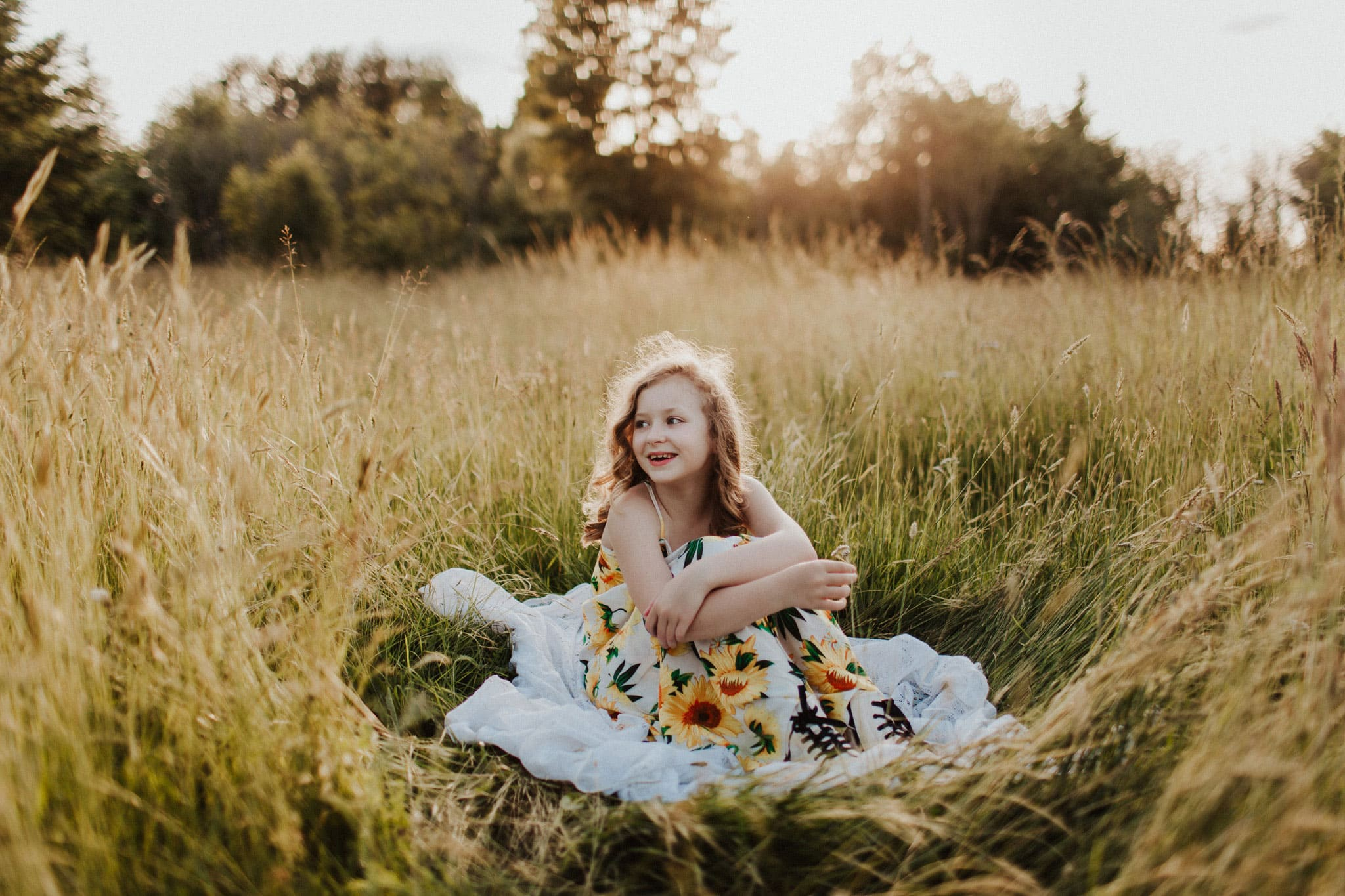smiling child on blanket in grass