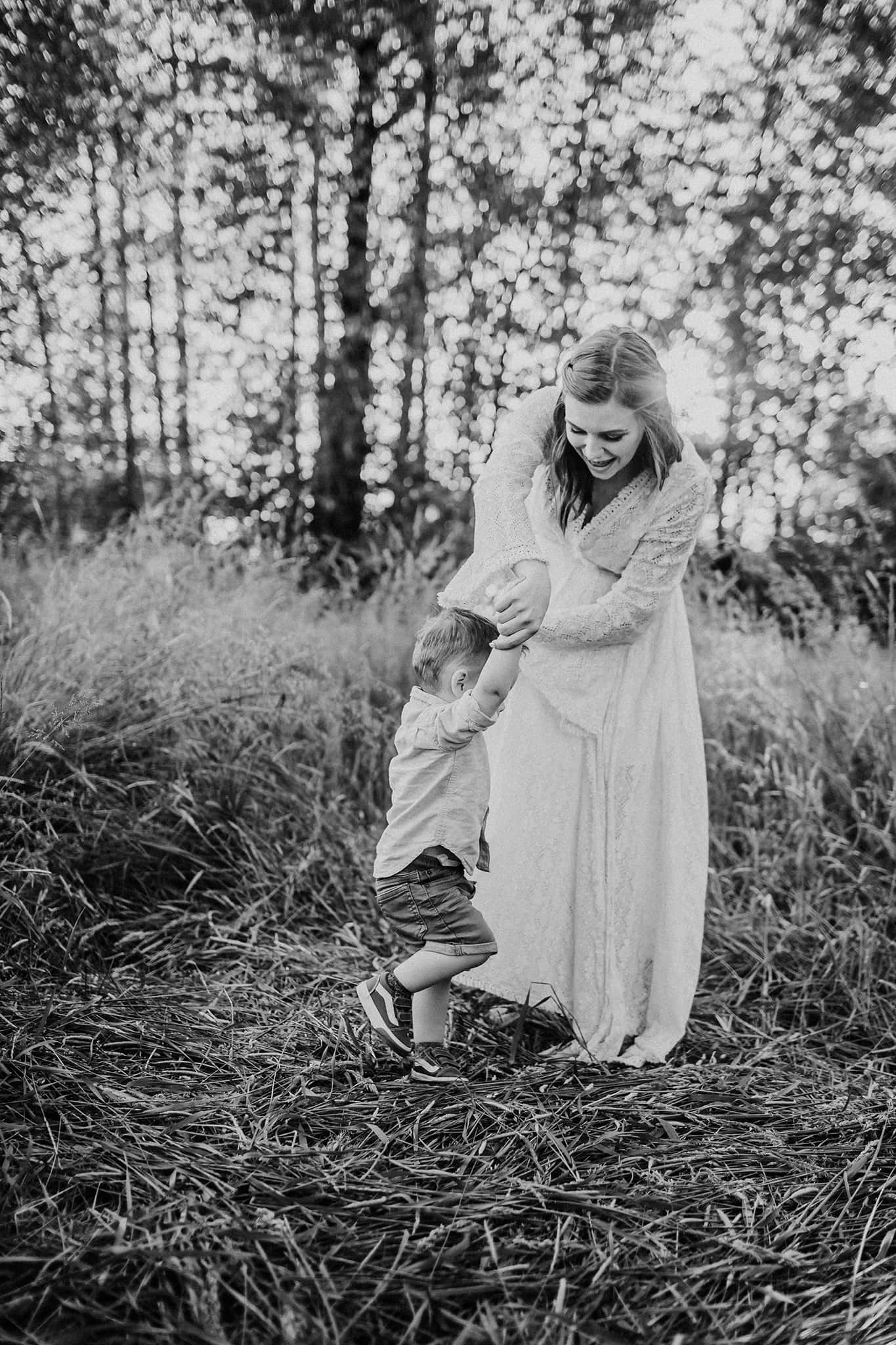 pregnant mom dancing with her son during maternity photo session