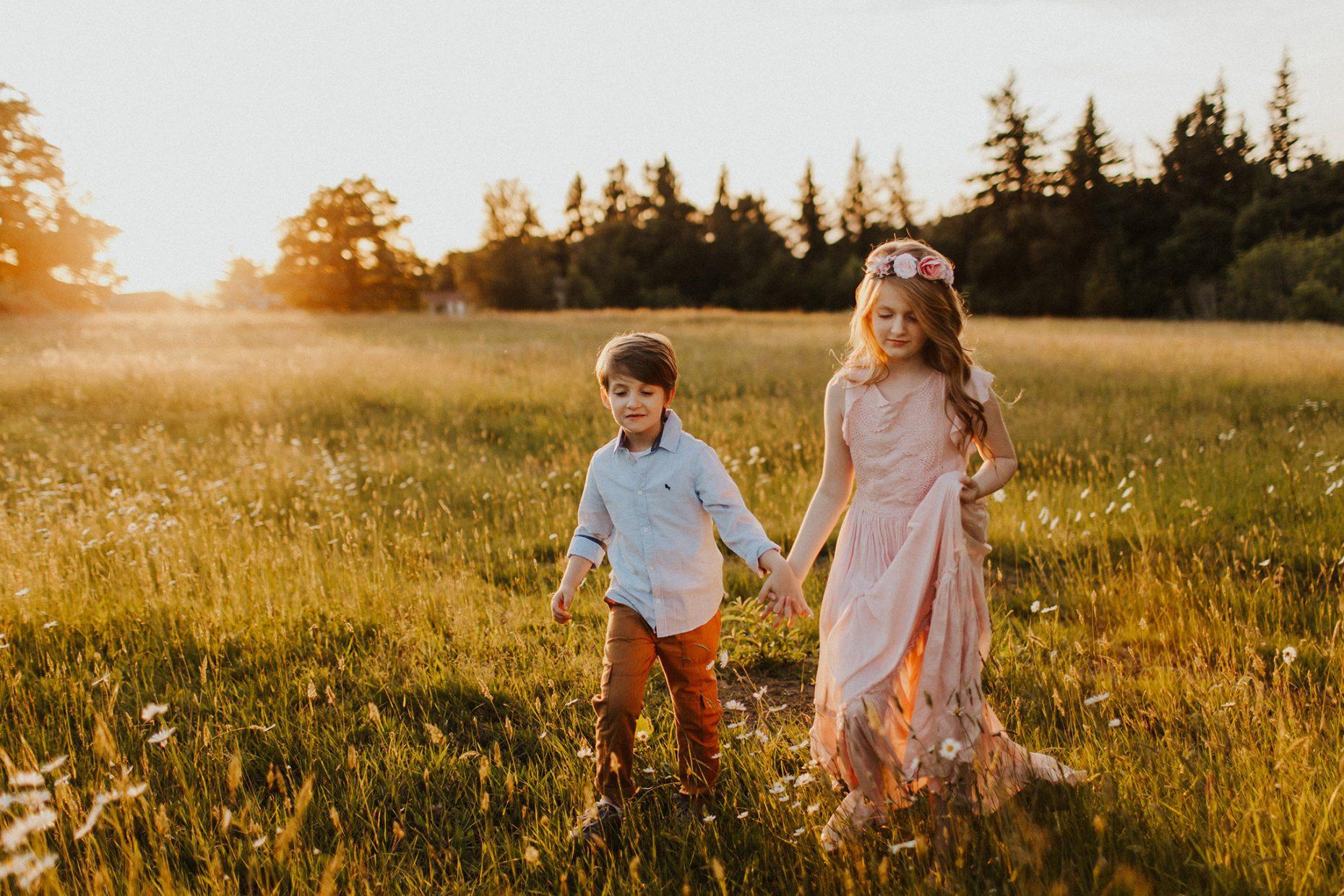 siblings walking in field of flowers - photo session in portland oregon