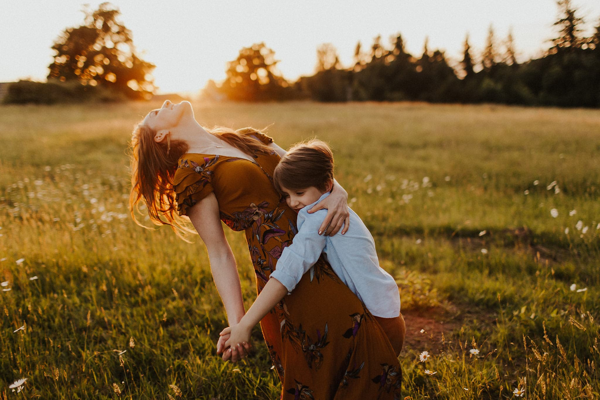 mom and son dancing in the sunset light - family photographers