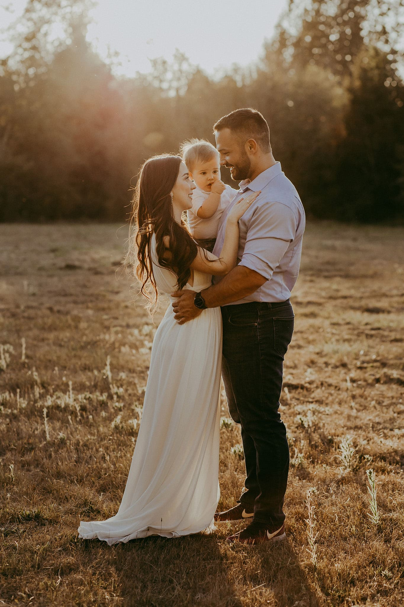 photos in the summer season - family of three embracing with the sun behind them