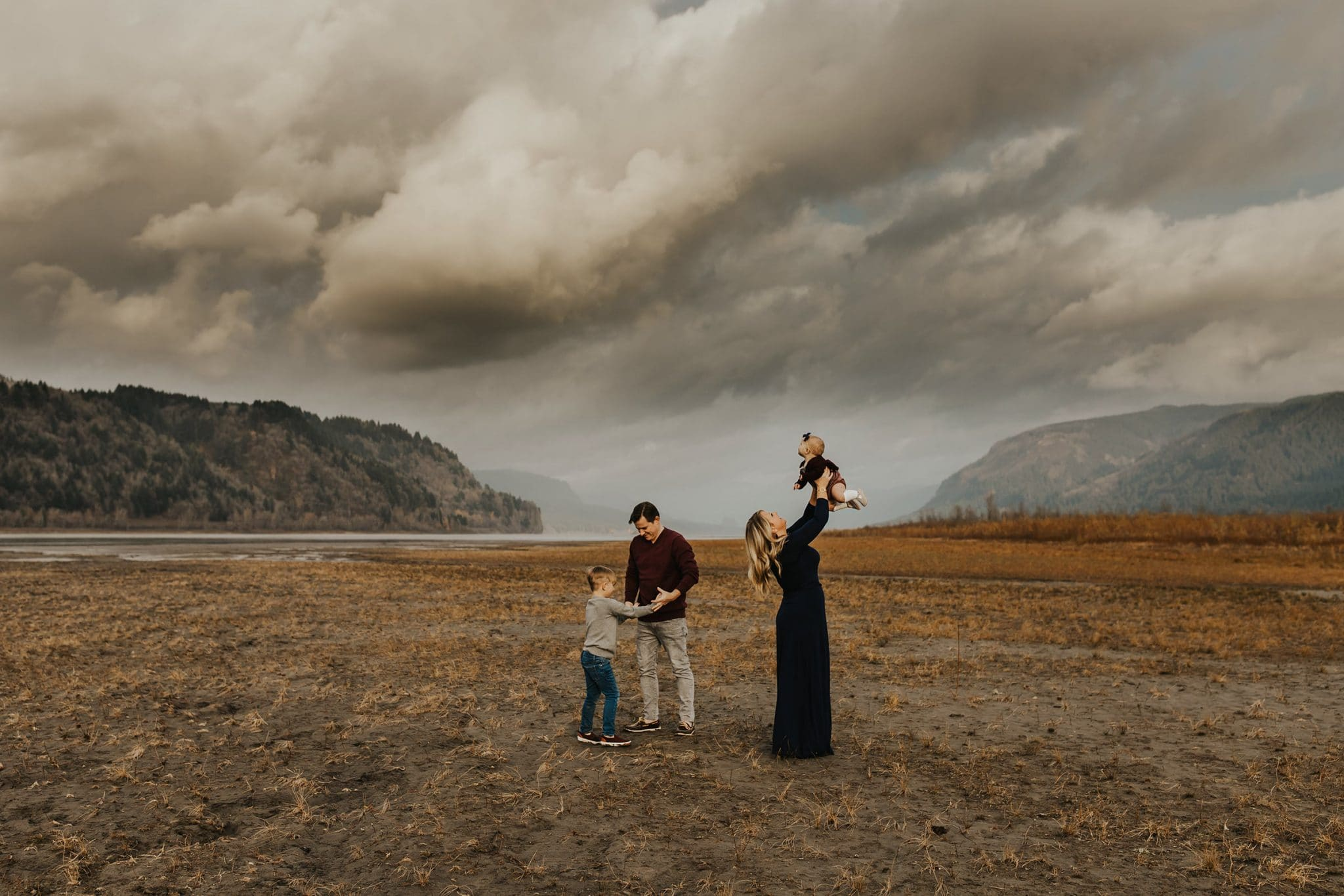 Family of four on a cloudy day with mountains behind them - southeast portland photographer family photos