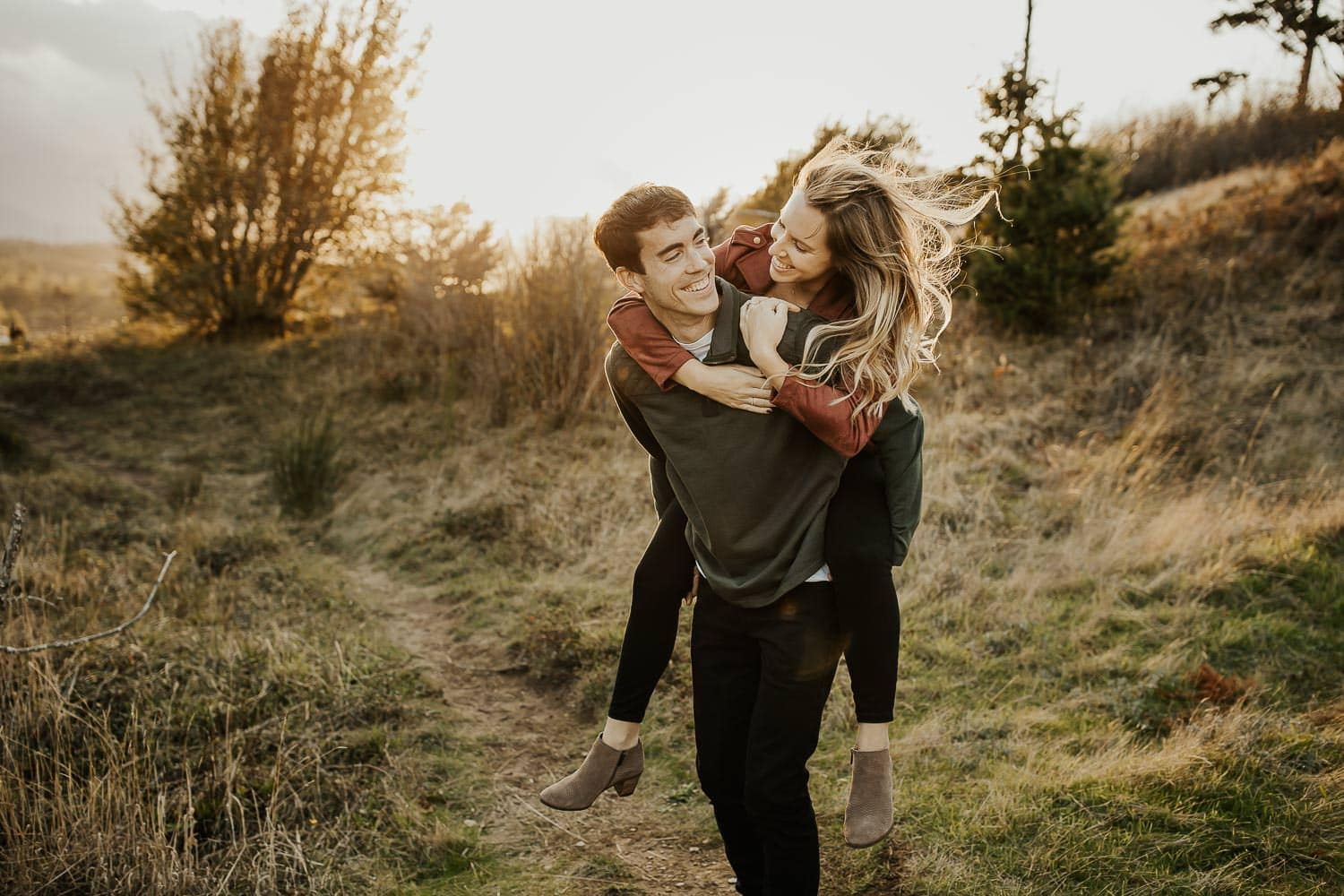 Couple having fun with a piggy back ride during anniversary photo shoot - date night ideas