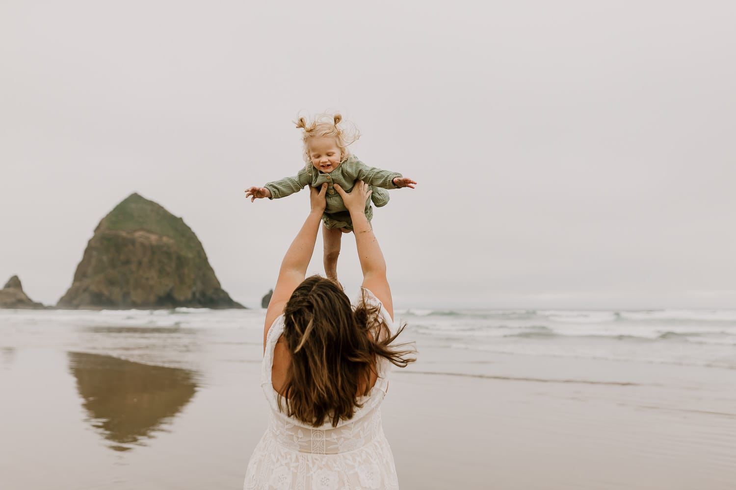 Mom holding her baby in the air like an airplane with haystack rock behind them during adventure family photos