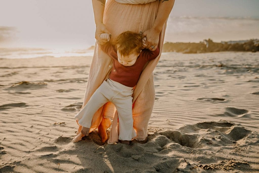 Mom in pink skirt holding baby girls hands while she walks on sand at the beach