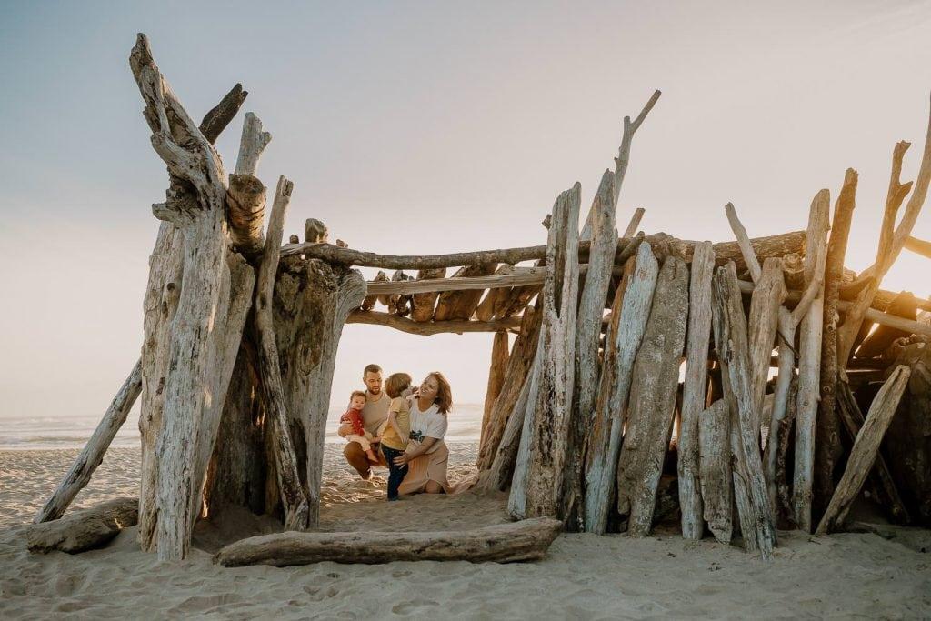 Family inside a driftwood hut in Rockaway Beach
