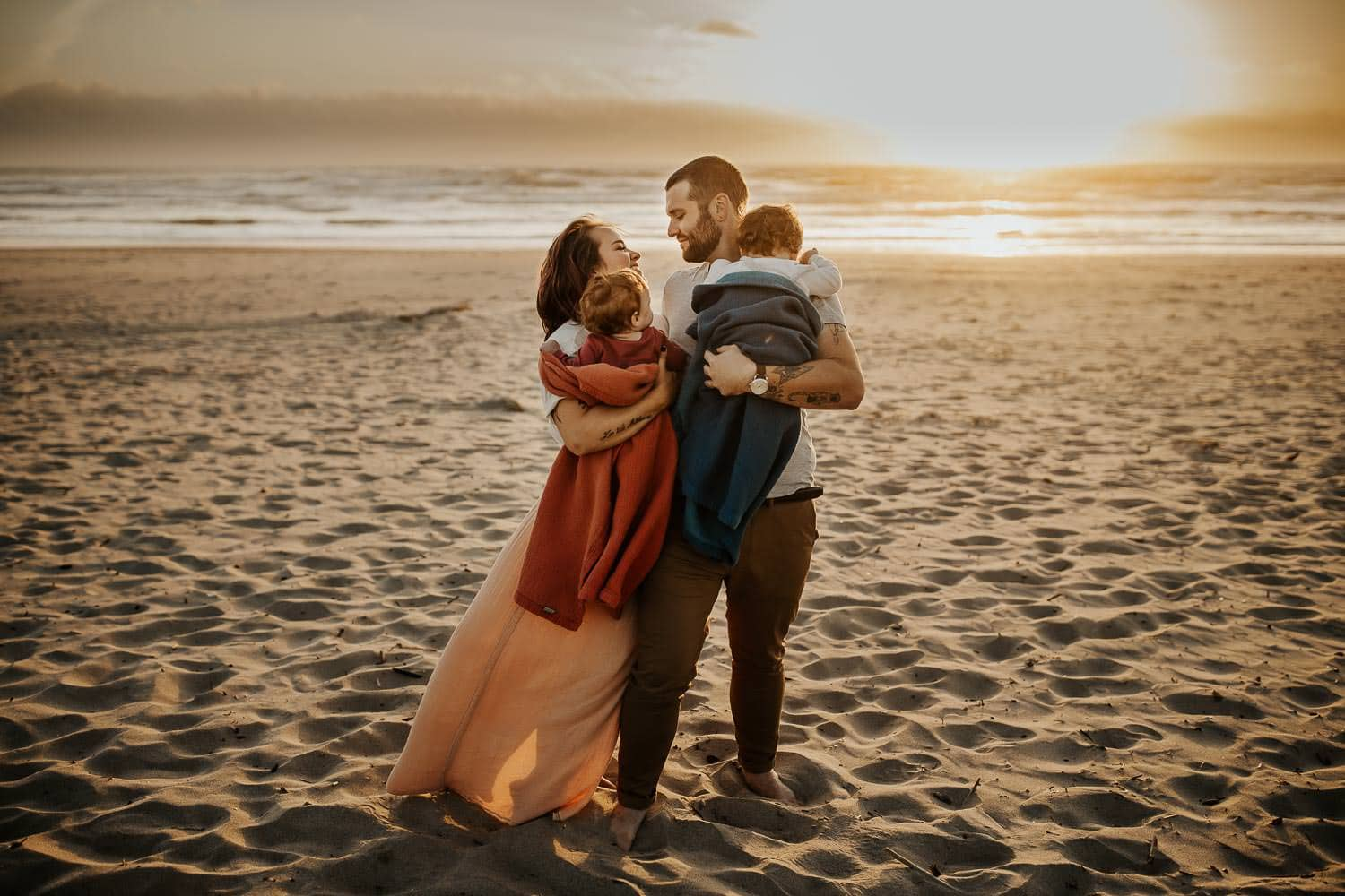 family of four standing on the beach with wind blowing - Oregon Coast Rockaway family photographer