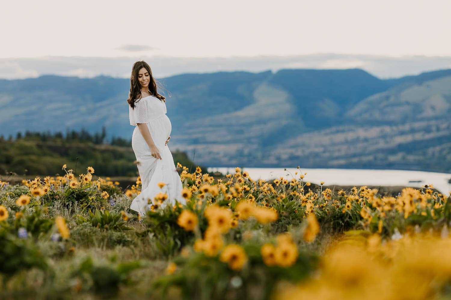 Beautiful pregnant woman in a white dress with wildflowers all around in the Columbia River Gorge