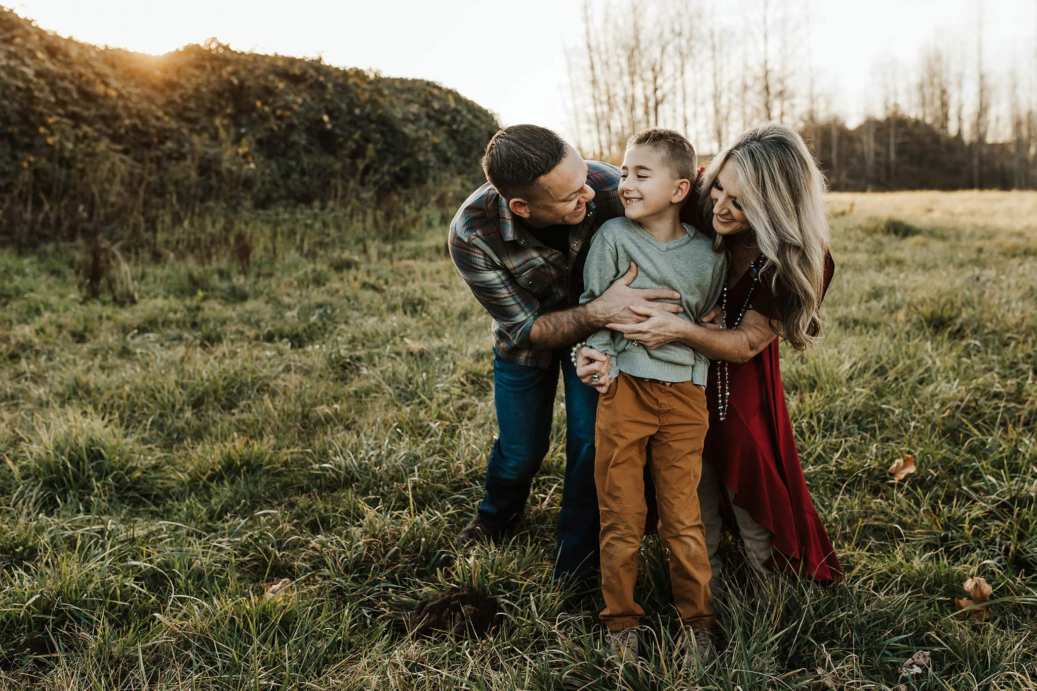 family laughing and looking at each other with parents arms around son