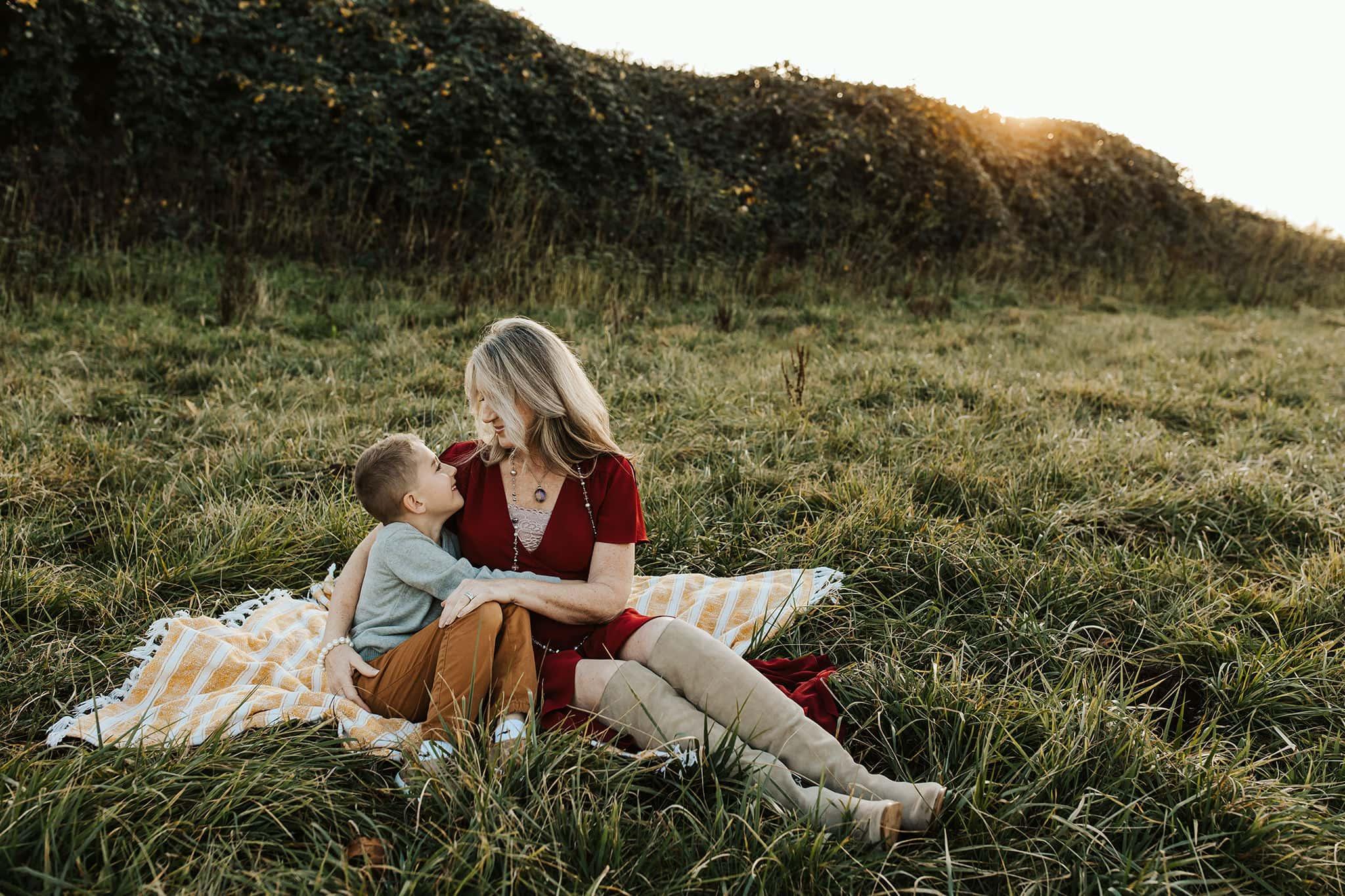 Mom cuddling son on blanket - candid family