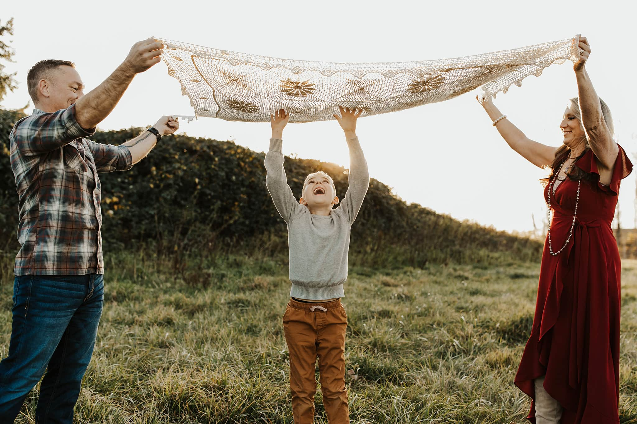 Son running under blanket