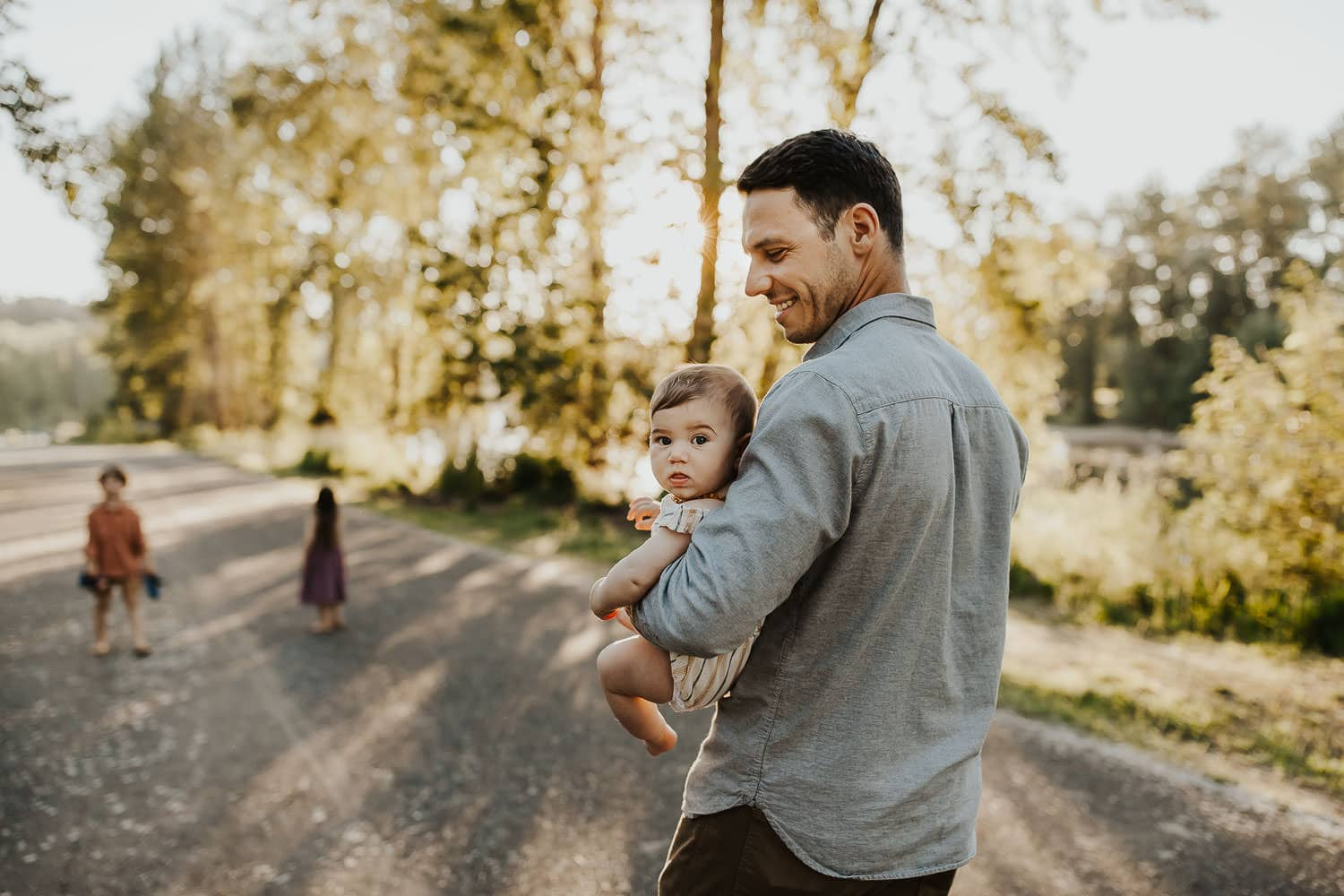 Dad holding baby girl while walking at a park in oregon city