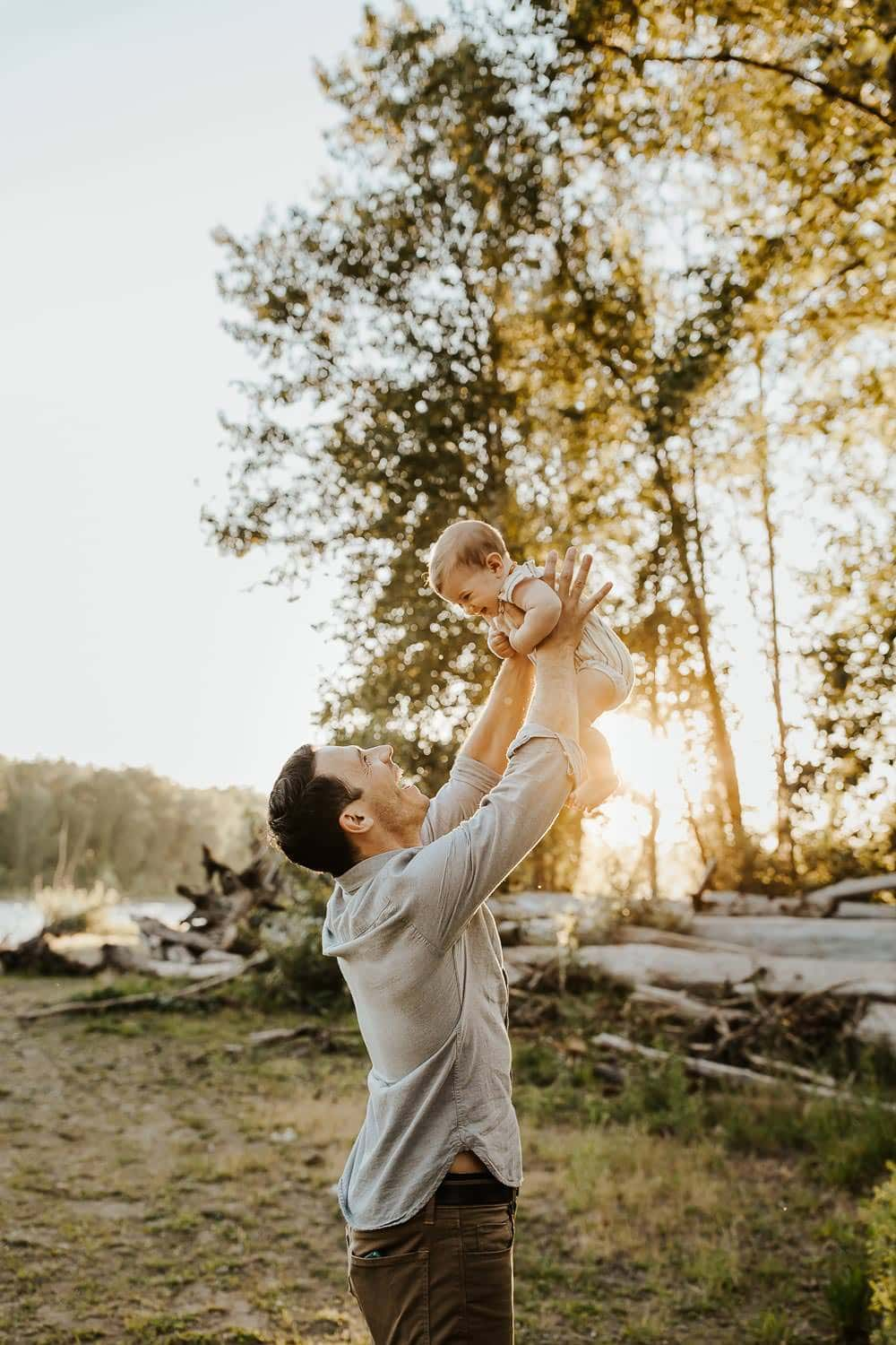 Dad lifting baby girl into the air during family session in Oregon City
