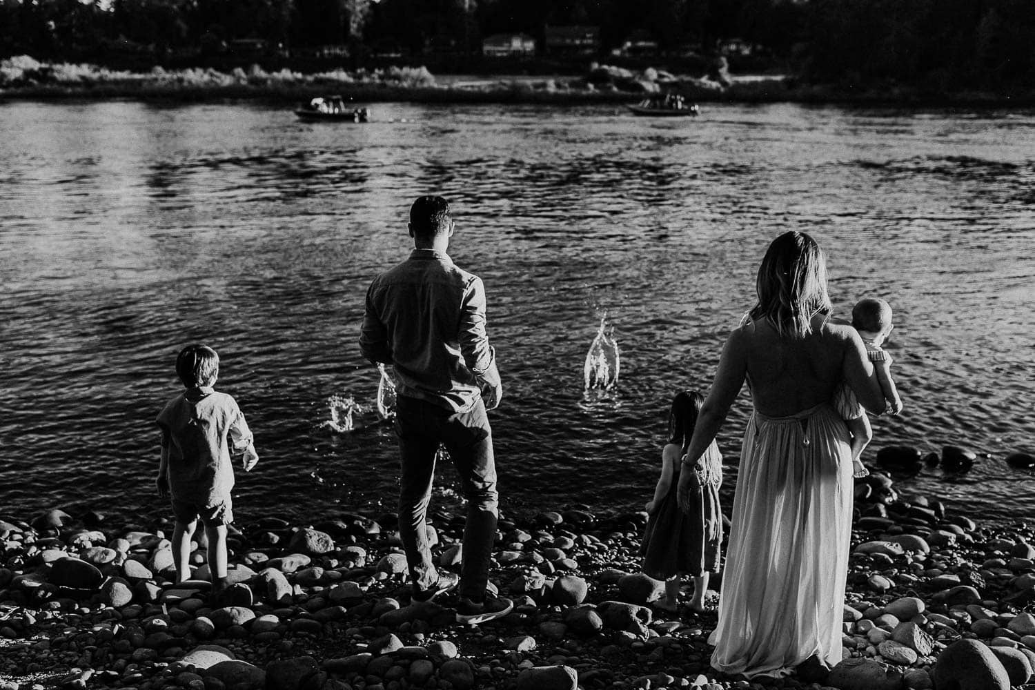 Family standing next to a river throwing rocks in - black and white image