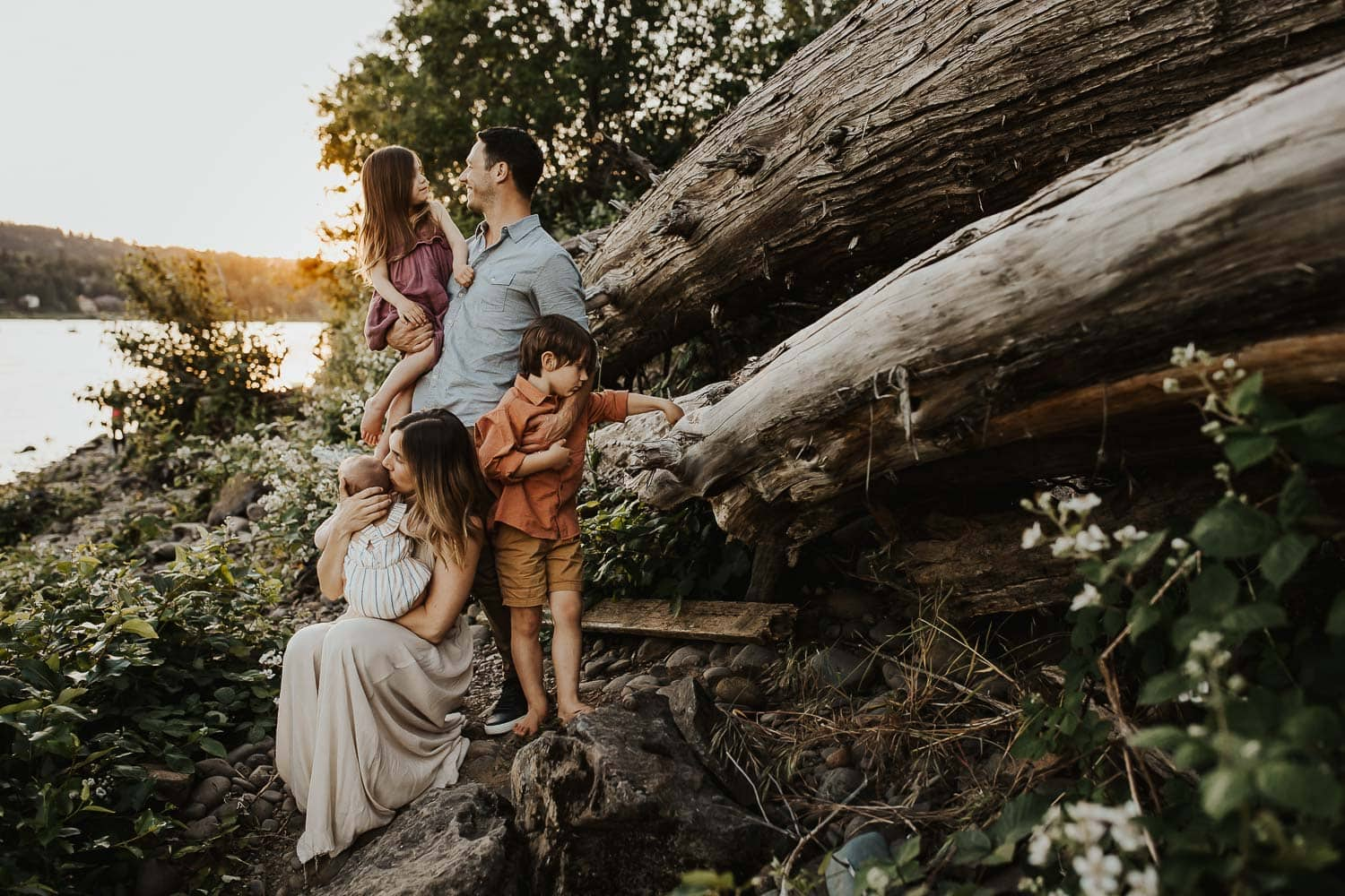 Best Portland Family Photographer - Family snuggling together next to a log