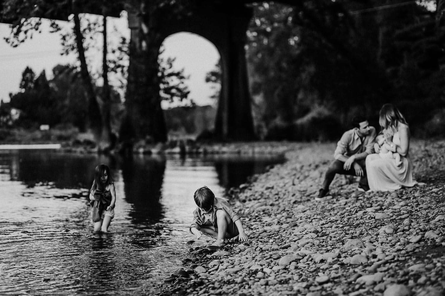 black and white image of family playing by the river in Oregon City