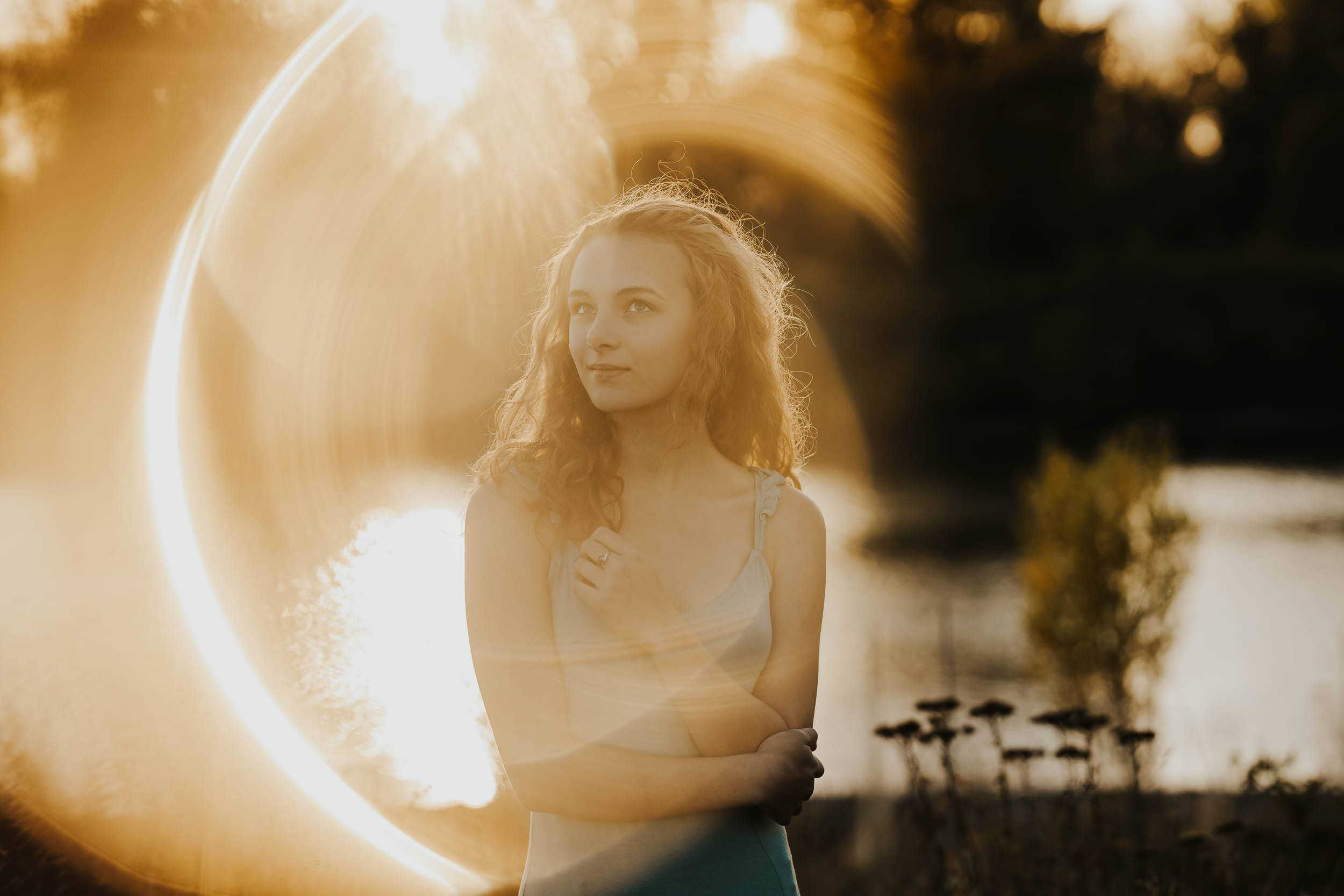senior girl in turquoise dress with golden ring around her, made by using a glass guitar slide