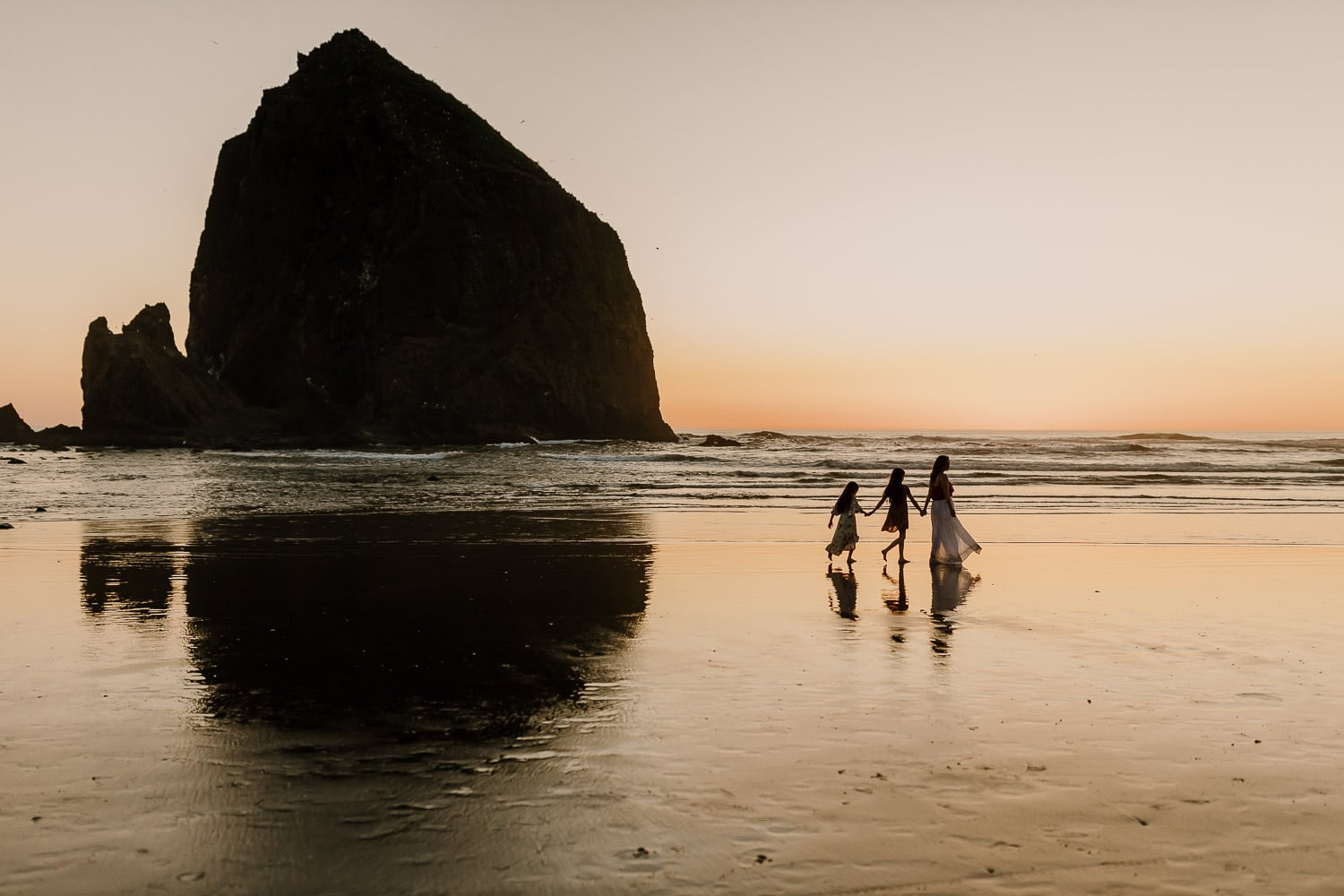 Mom and her two daughters walking past haystack rock in Cannon Beach