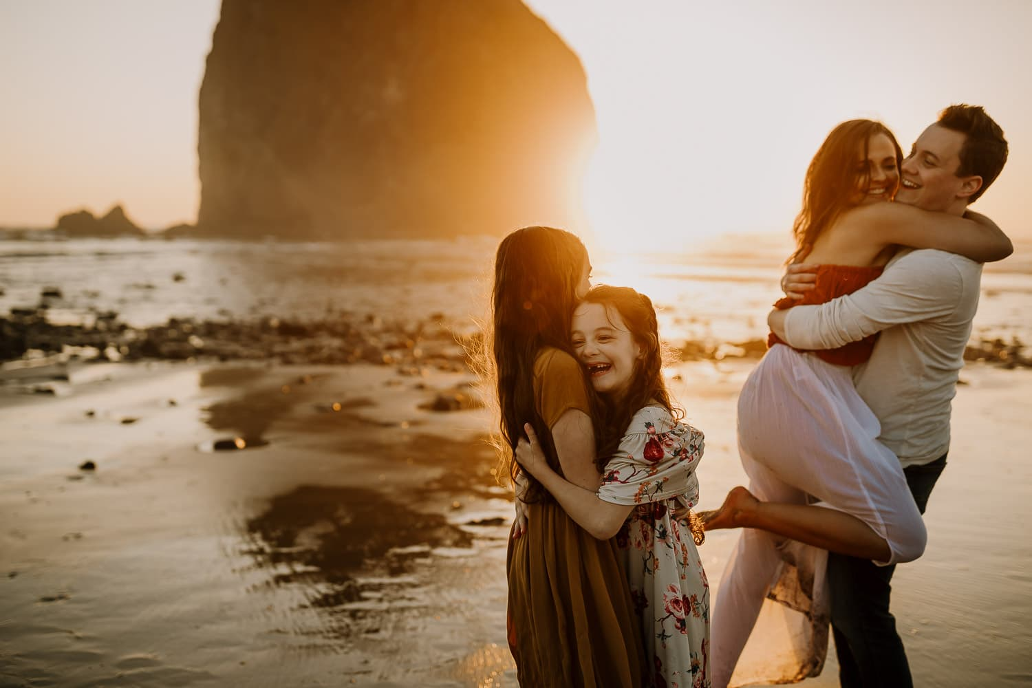 Couple hugging and laughing while their daughters hug and laugh too at sunset in Cannon Beach