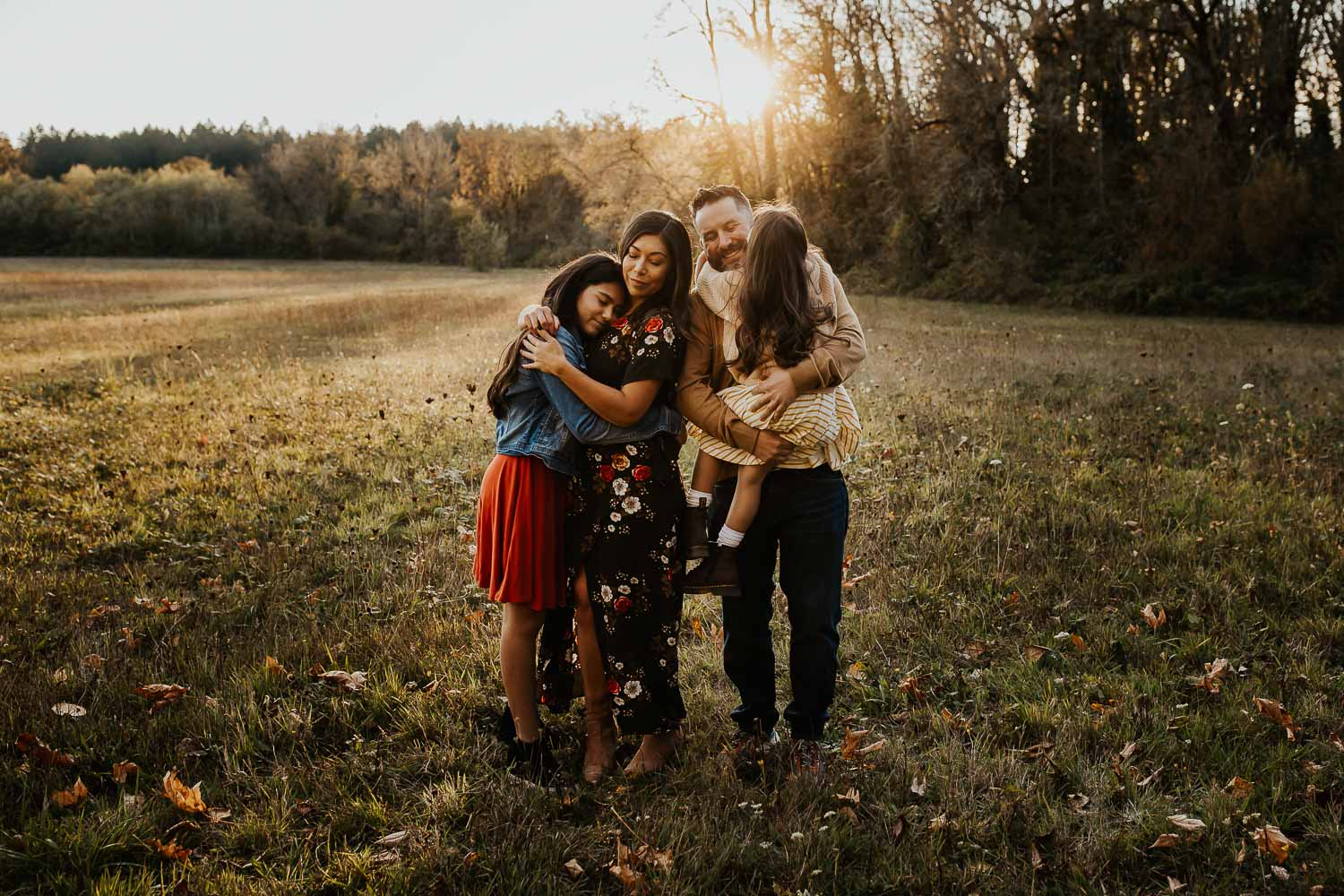 Family of four with two daughters hugging in a field