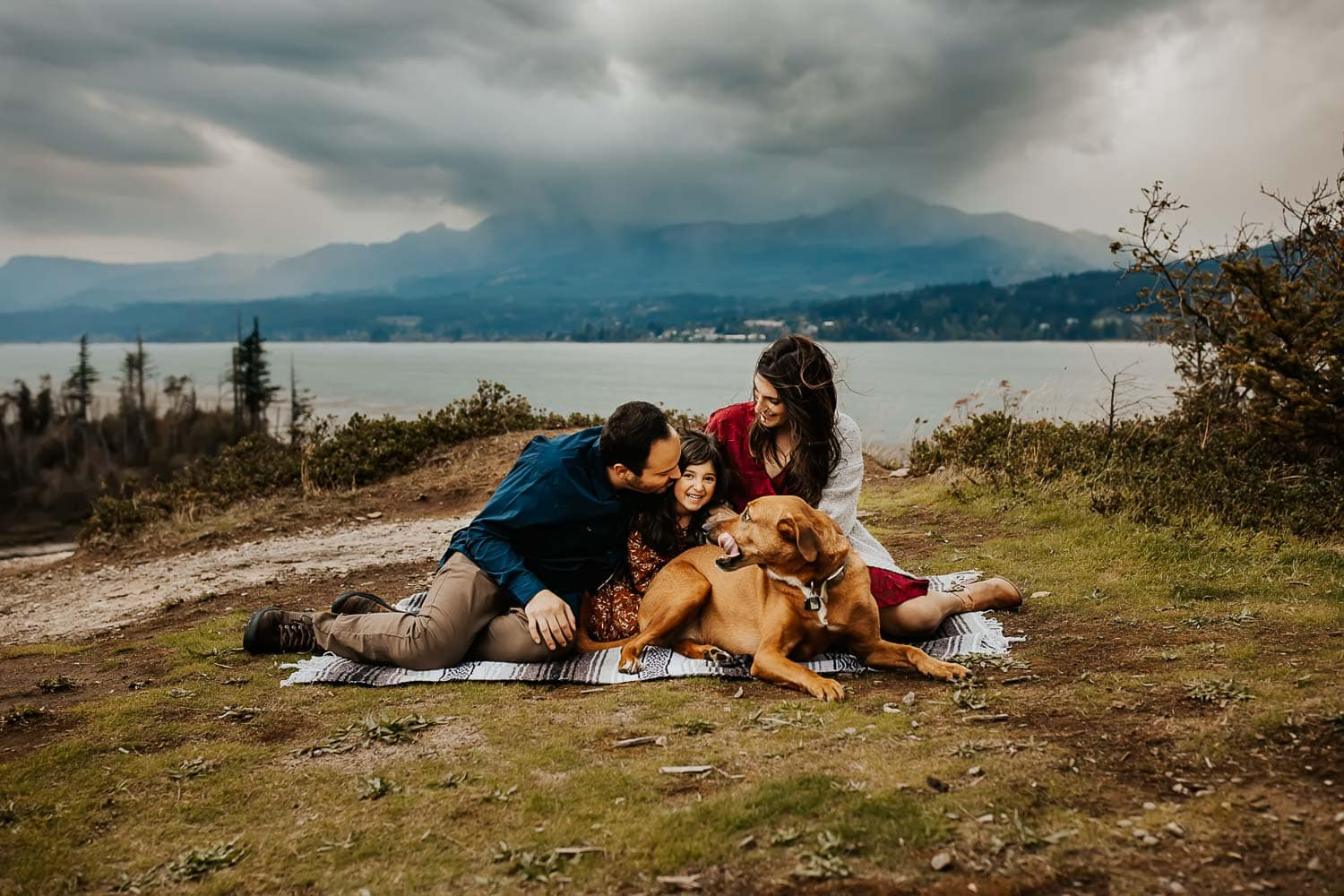 Family cuddling on blanket with their dog on a cloudy day