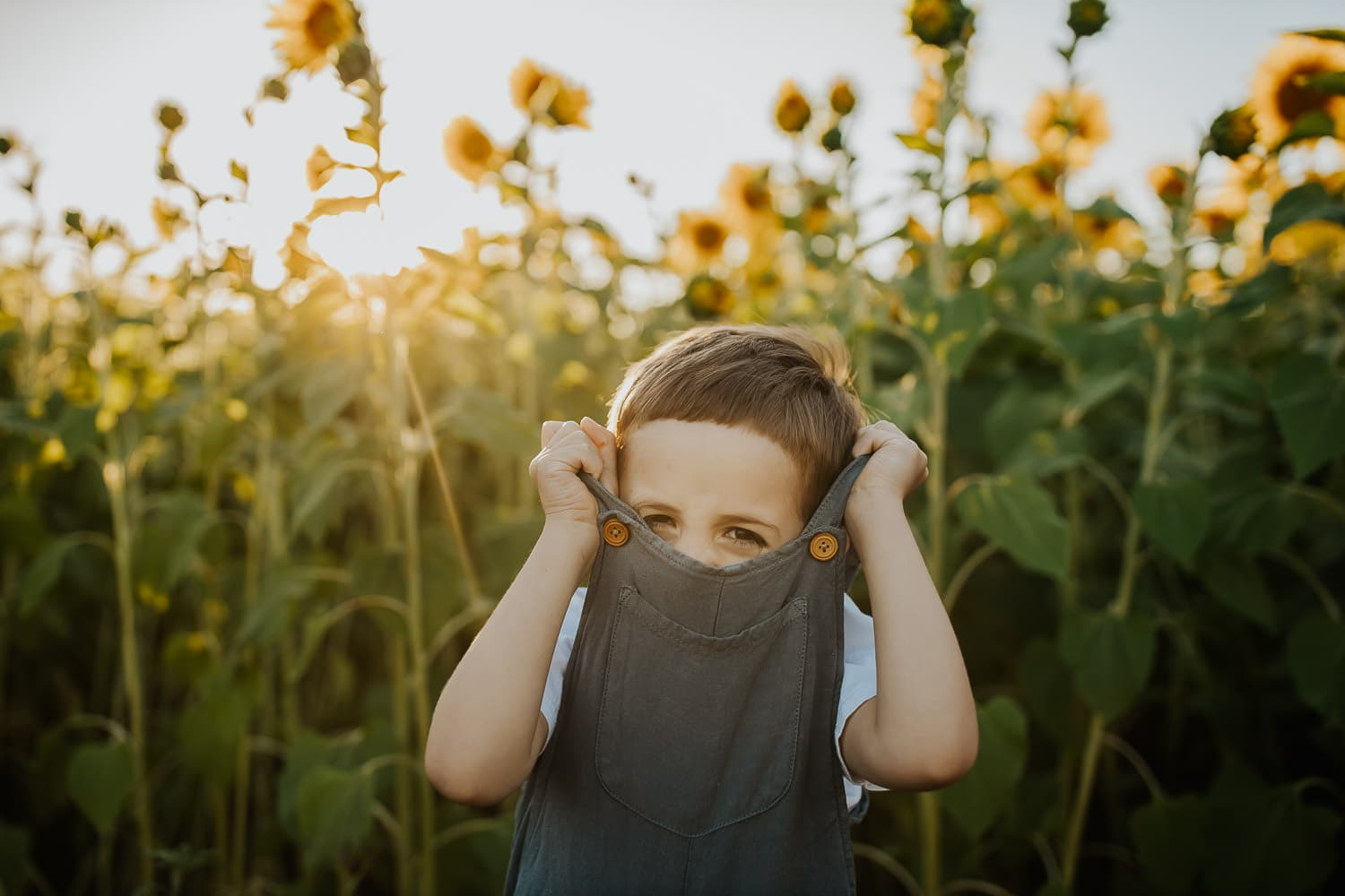 Toddler boy peeking his eyes out of his overalls - portland Oregon family photography