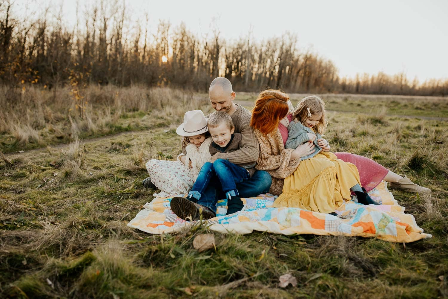 Family sitting on blanket together tickling each other - Portland photographer